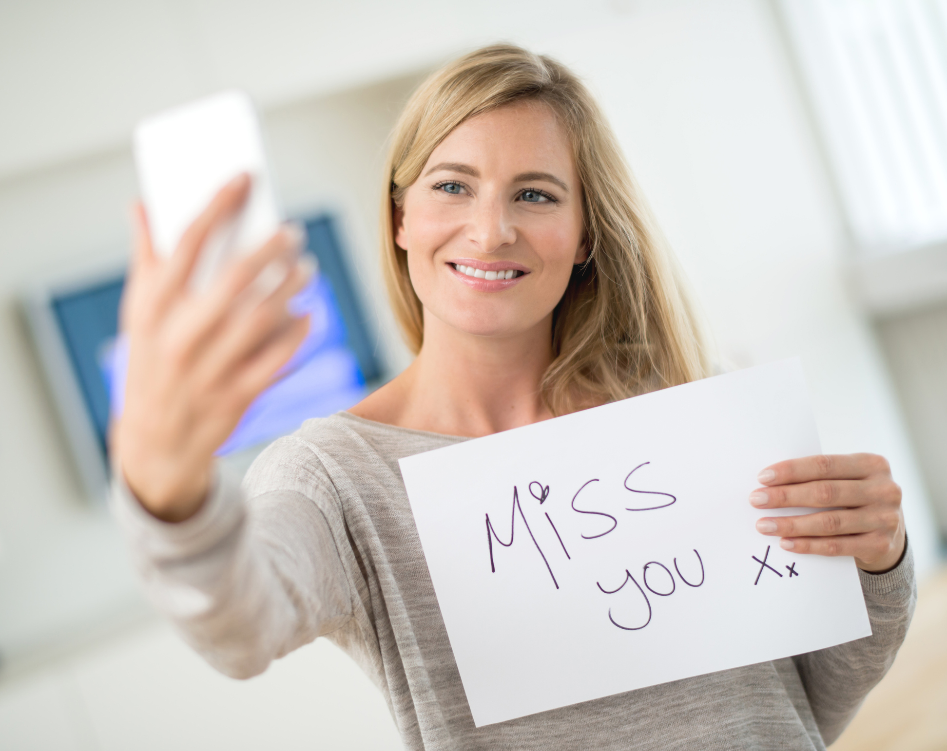 "Woman talking on web chat through her phone holding a sign saying ""miss you"" - distance relationship concepts"