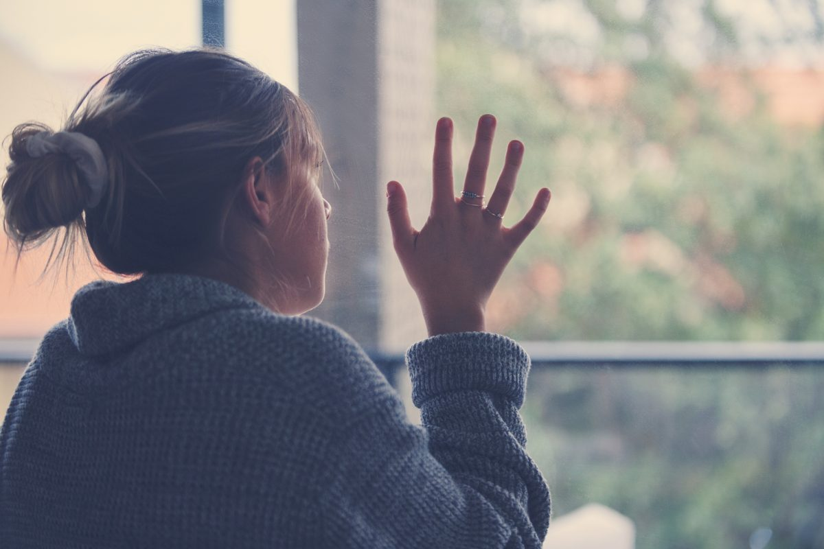 woman staring out window, sad