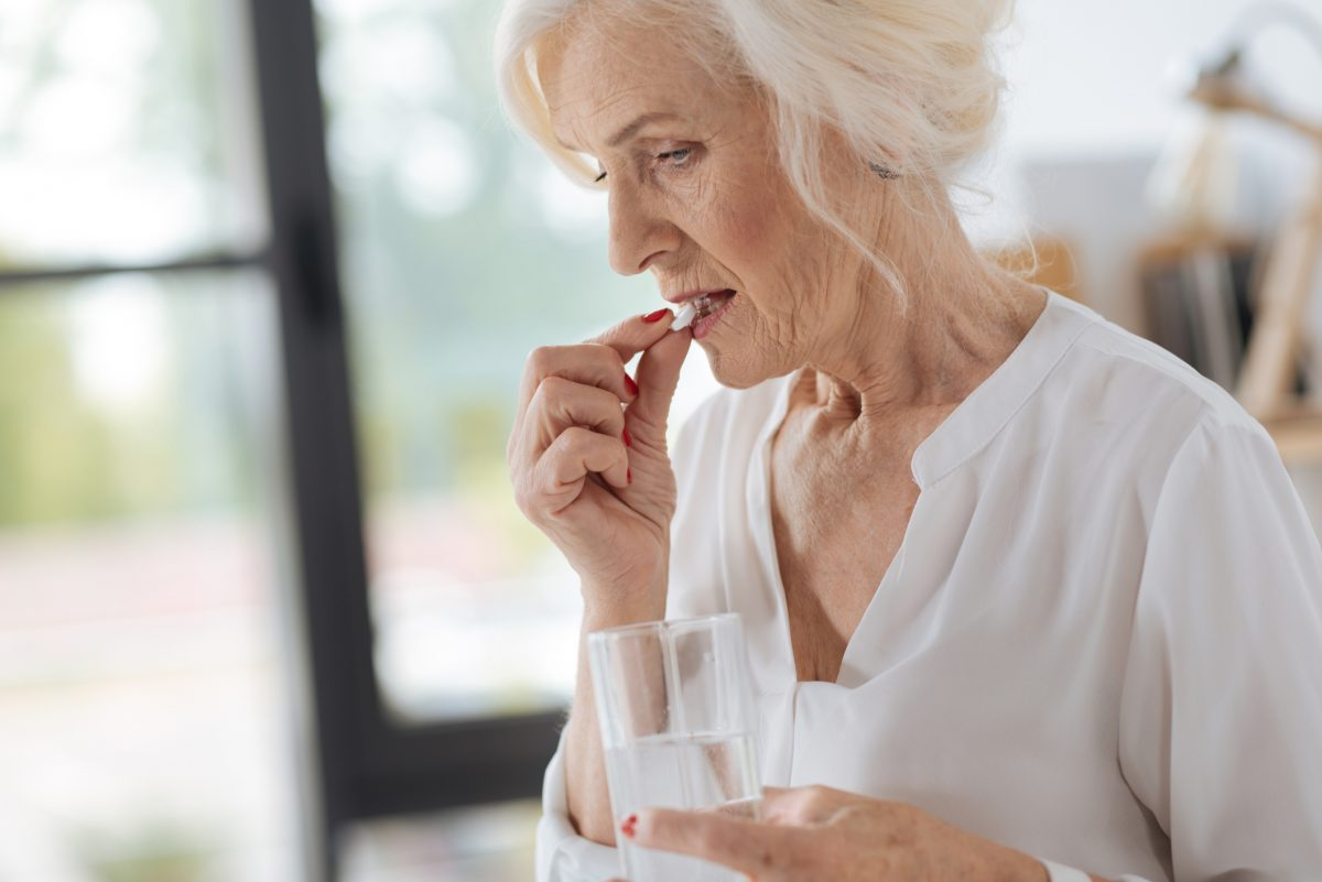 older woman taking pill