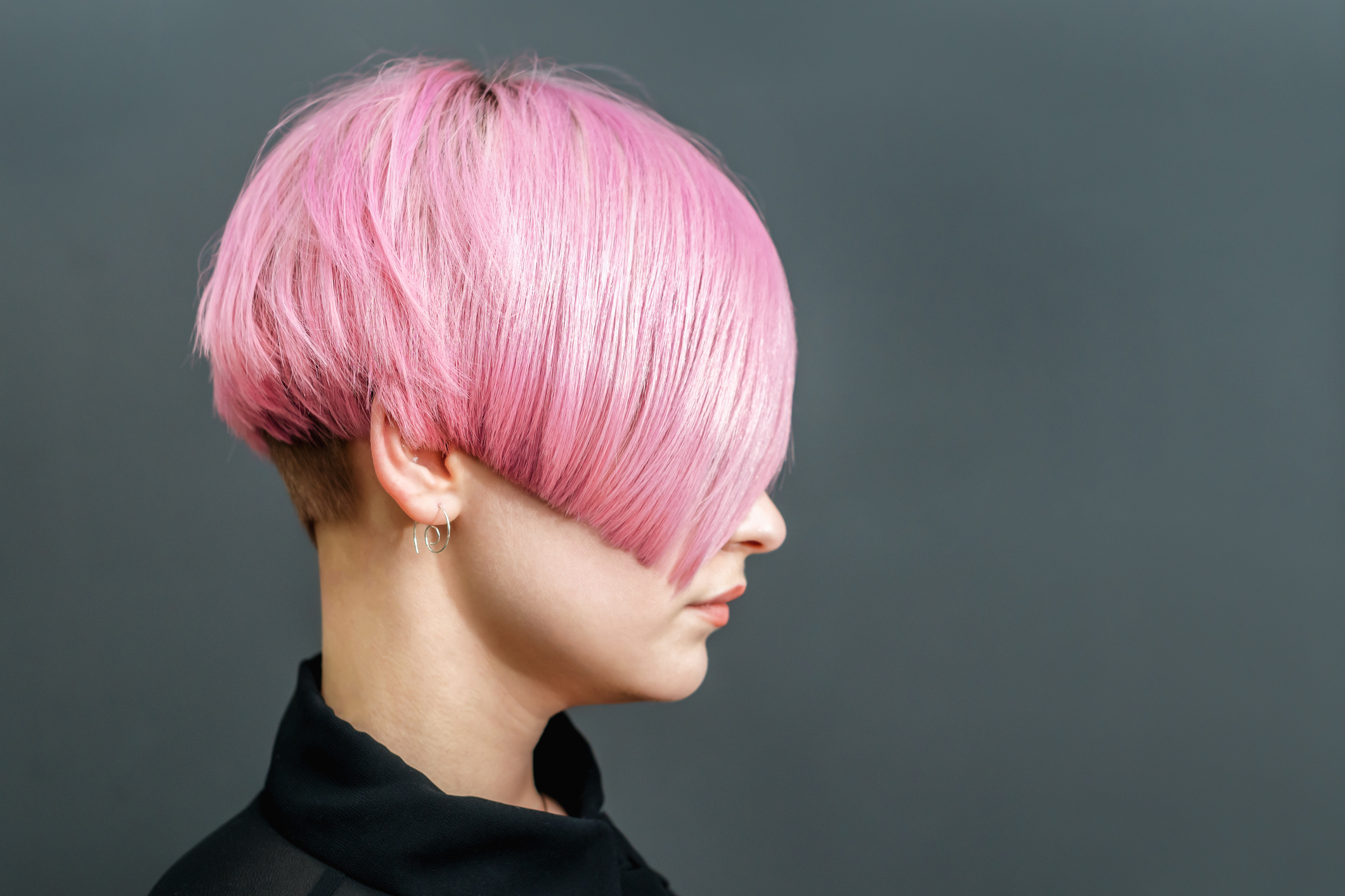 Beautiful model woman with short pink hairstyle on gray background.