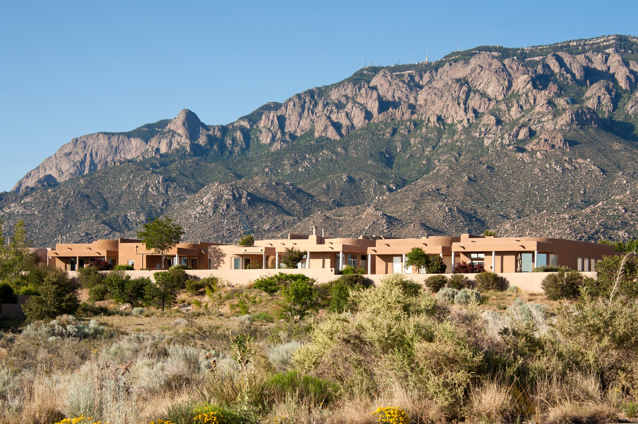 """""""Attractive, contemporary Southwestern residential architecture mountain background and beautiful blue sky."""""""