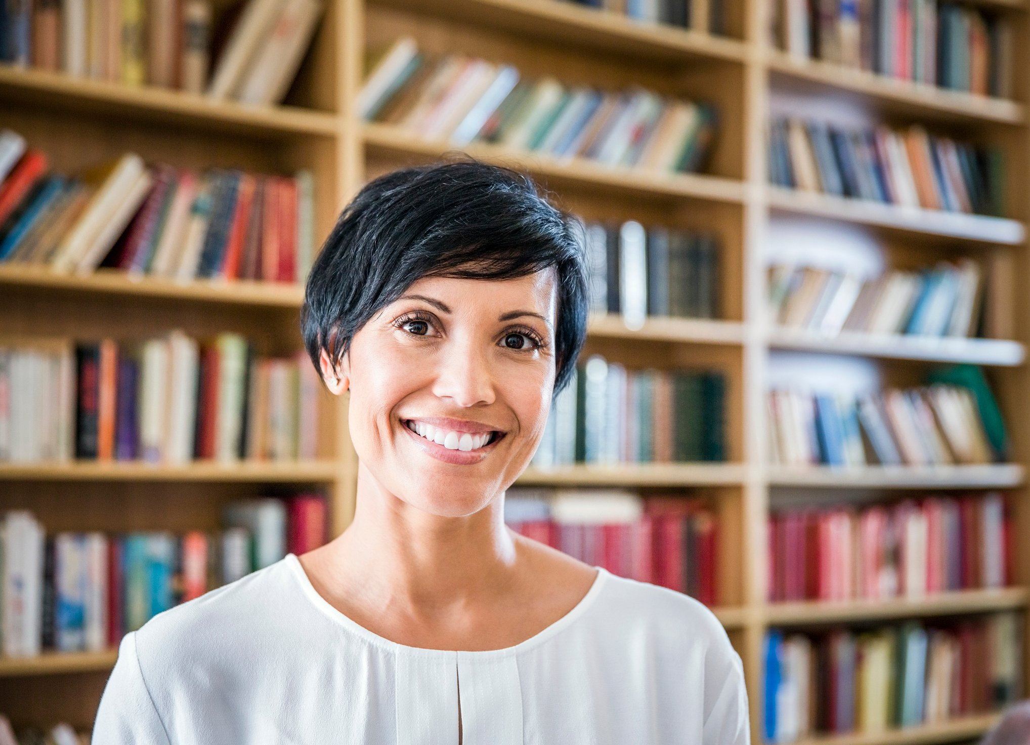 Portrait of confident woman smiling in library