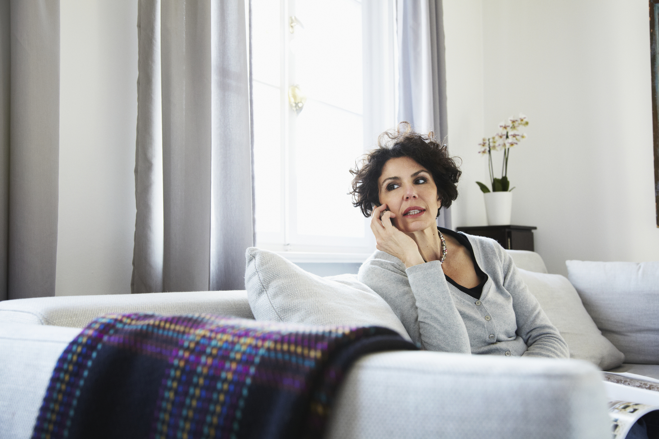 Woman on sofa and talking on cell phone
