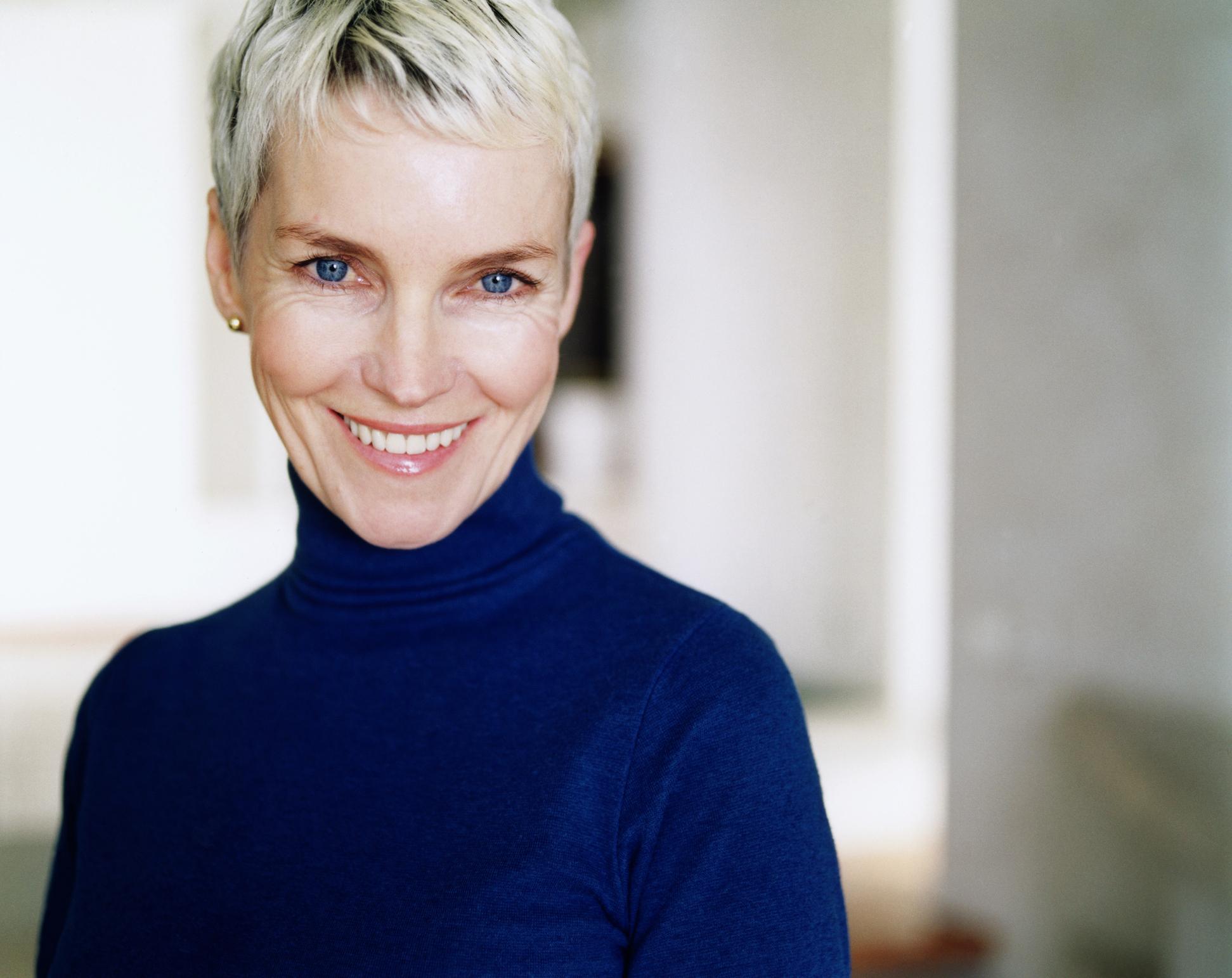 Mature woman wearing blue polo neck, portrait, close-up