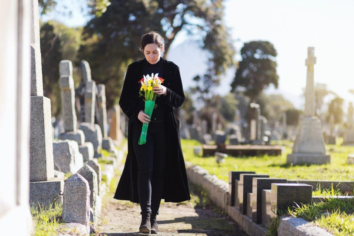woman walking graveyard bouquet