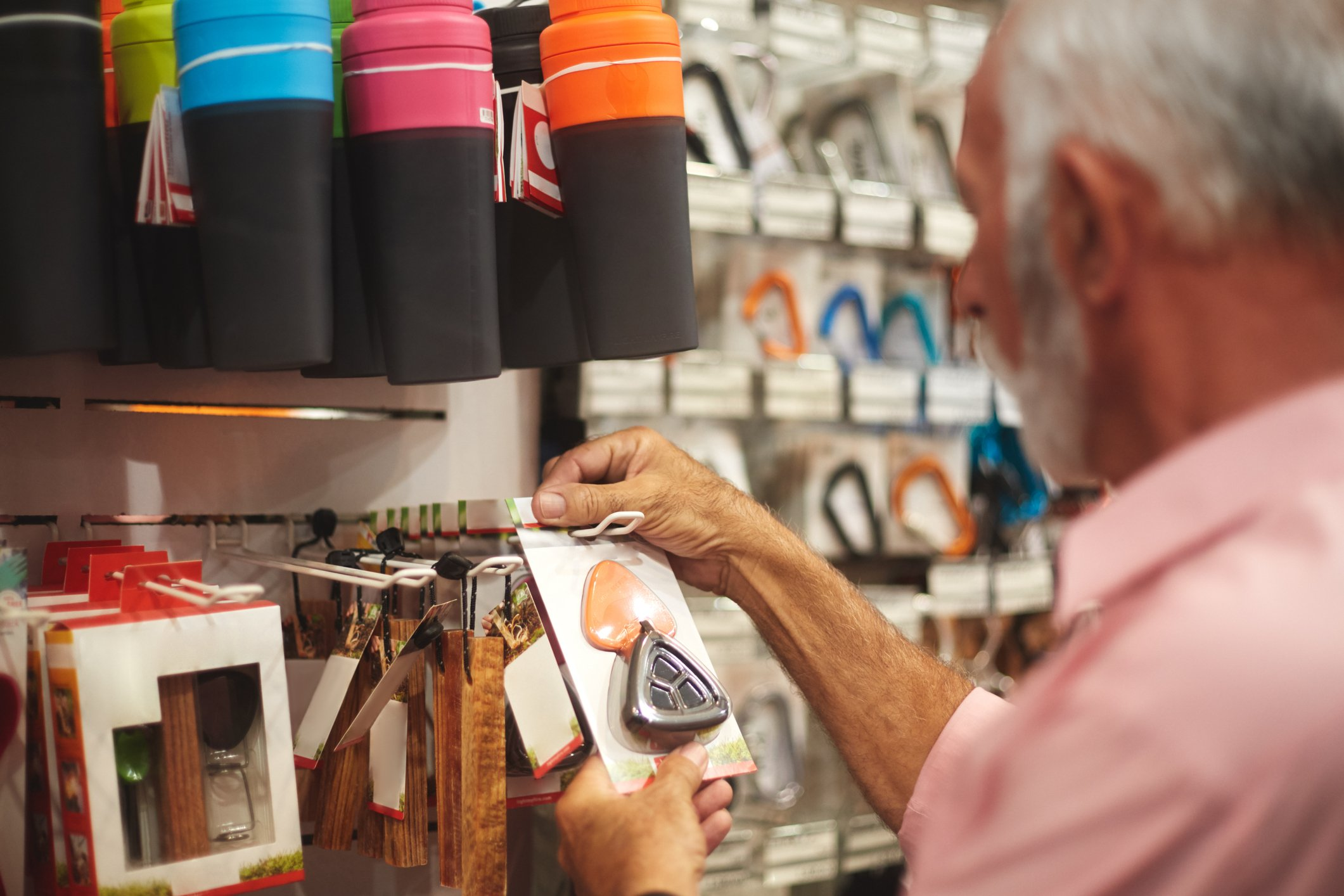 Senior man in sports and outdoor equipment store choosing to buy a flint.