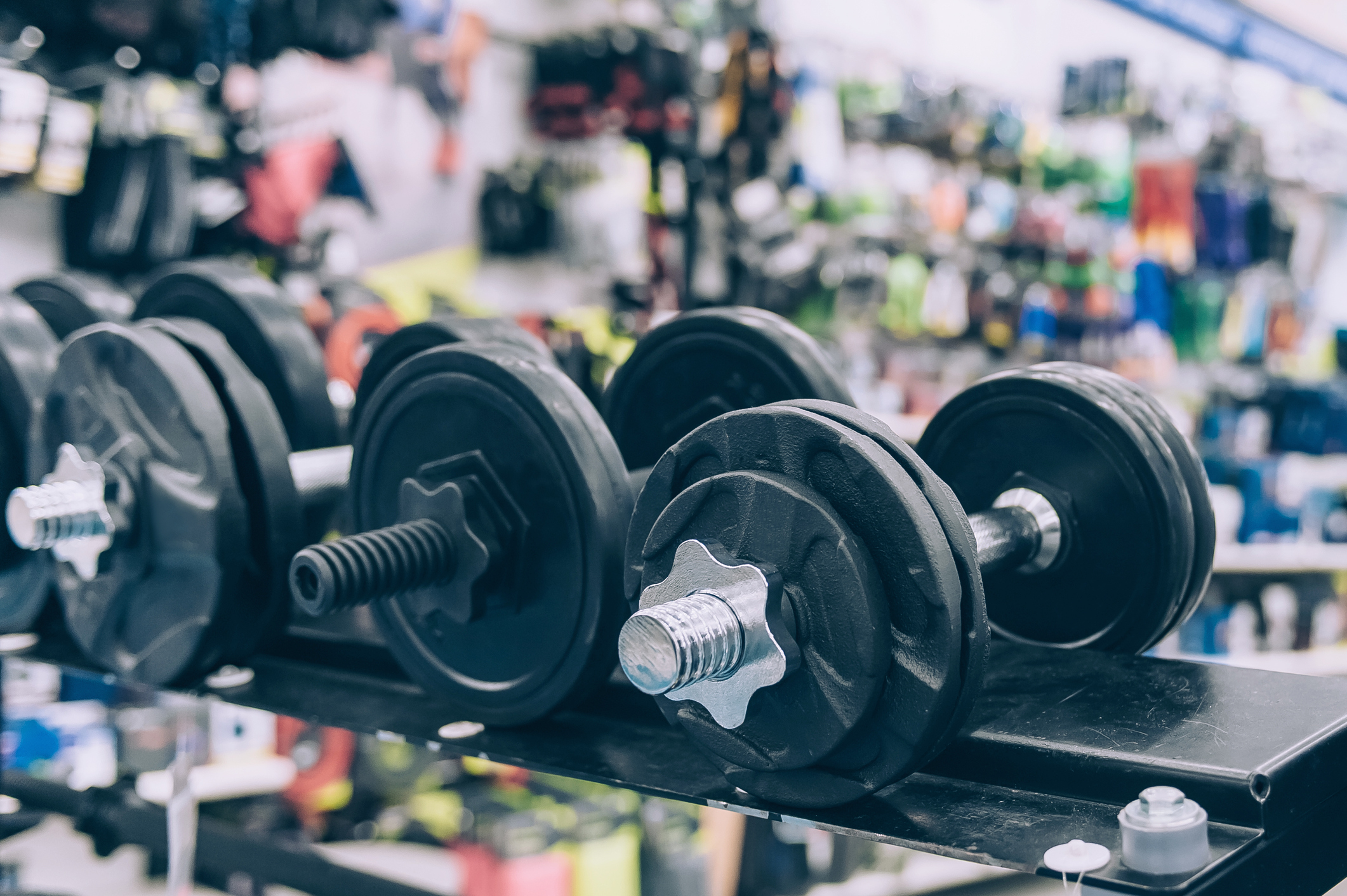 The guy holds a dumbbell in his hands at the sports store on the background of accessories for fitness