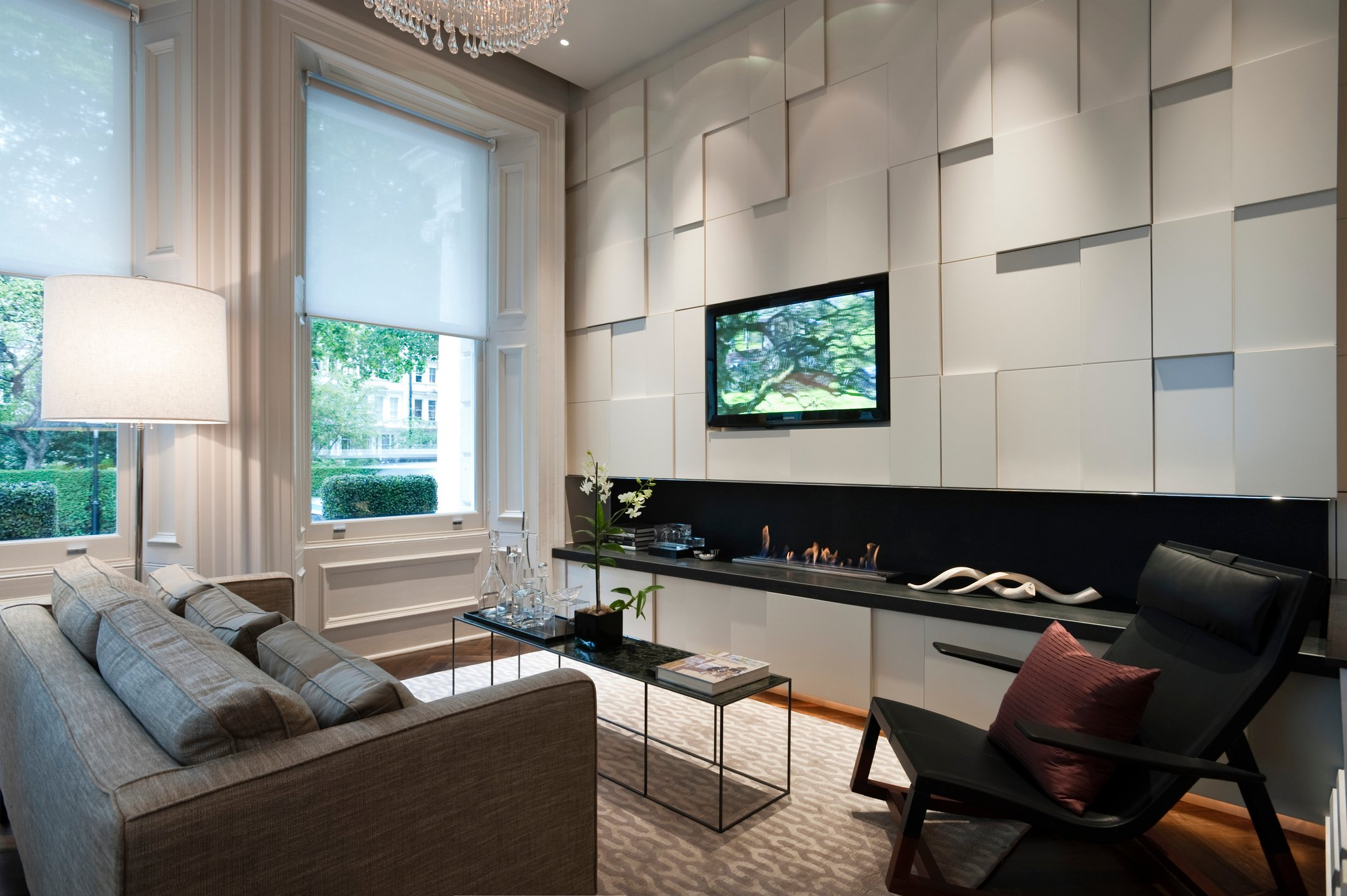 Seating area with plasma screen and recessed fire in London city apartment