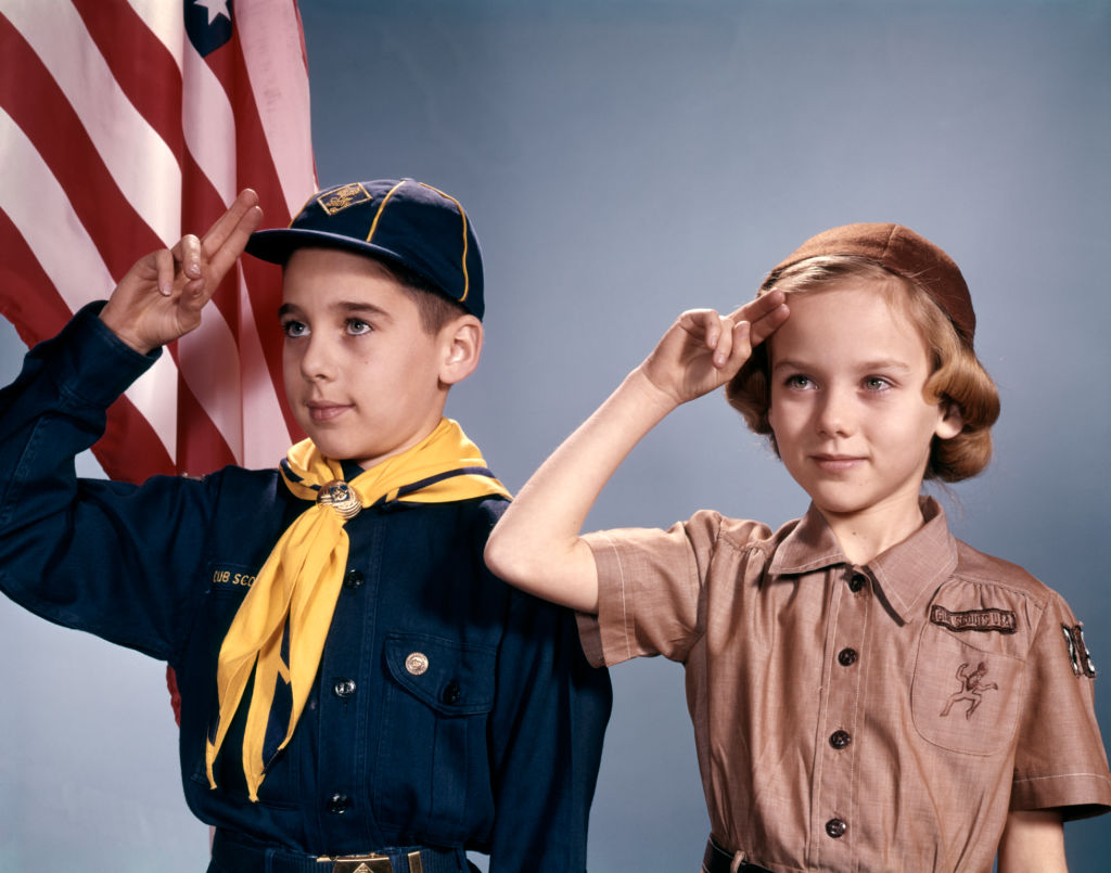 1960s BOY AND GIRL IN CUB SCOUT AND BROWNIE UNIFORMS STANDING BY AMERICAN FLAG SALUTING