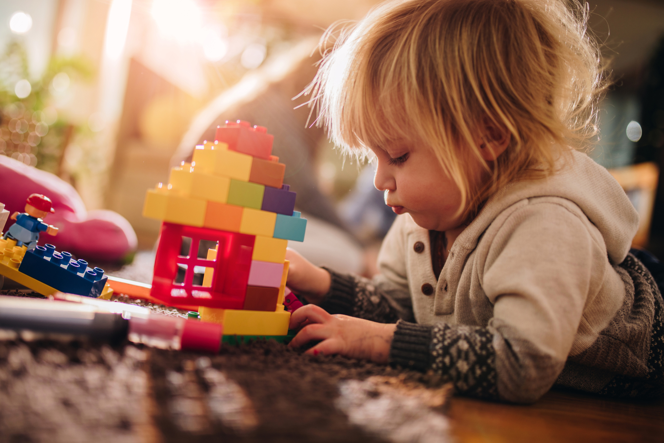 Cute kid stacking toy blocks while relaxing on the floor at home. There are people in the background.