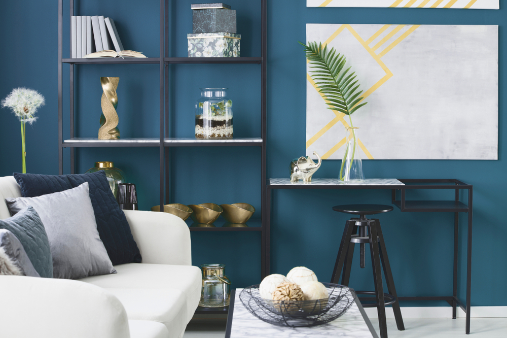Gold elephant and a leaf in a glass vase placed on marble desk in blue living room interior with decor on metal rack