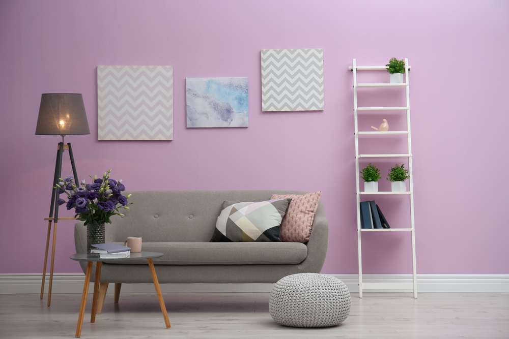 Modern living room interior with comfortable gray sofa near color wall