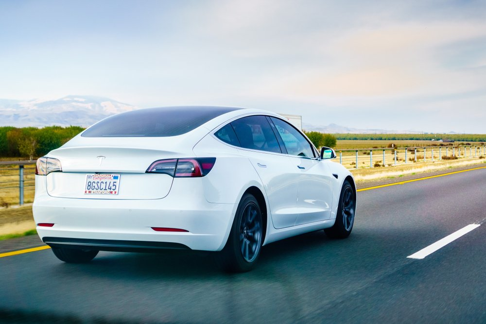 White Tesla Model 3 driving on the freeway