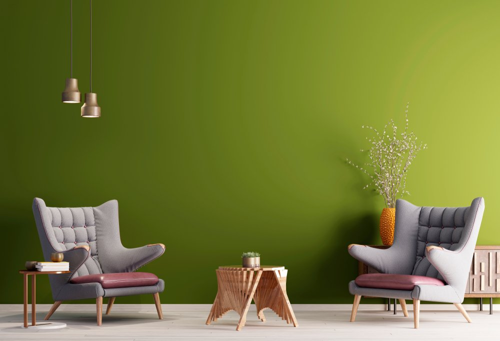 Two armchair in a green color background wall, living room in modern style with low table and decor.