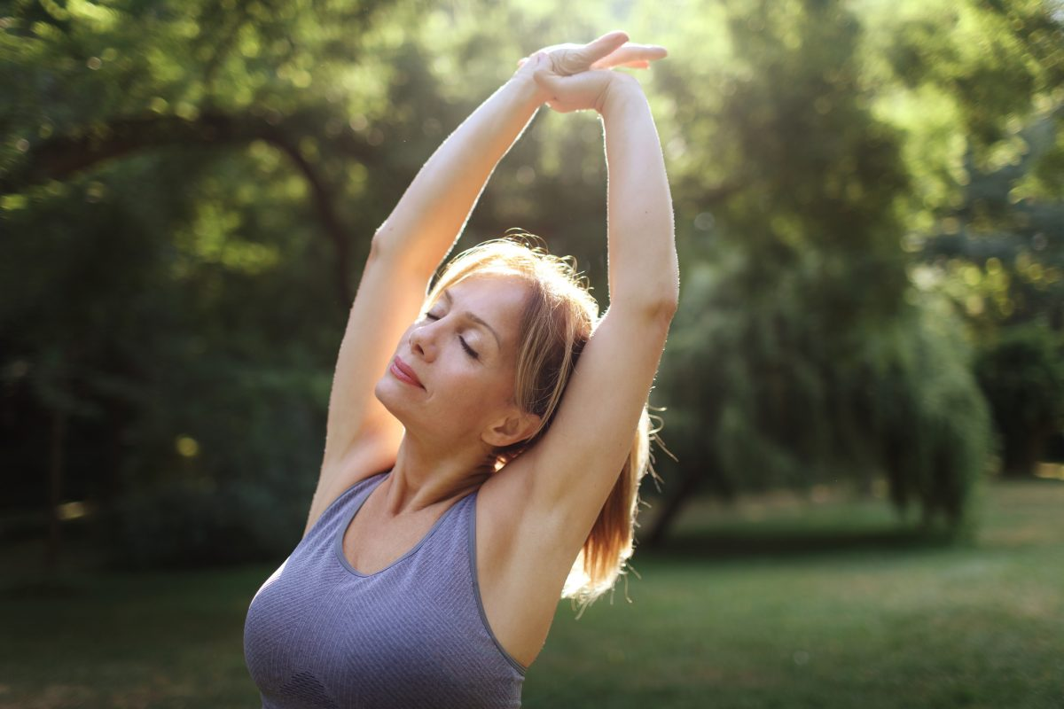 woman stretches outside