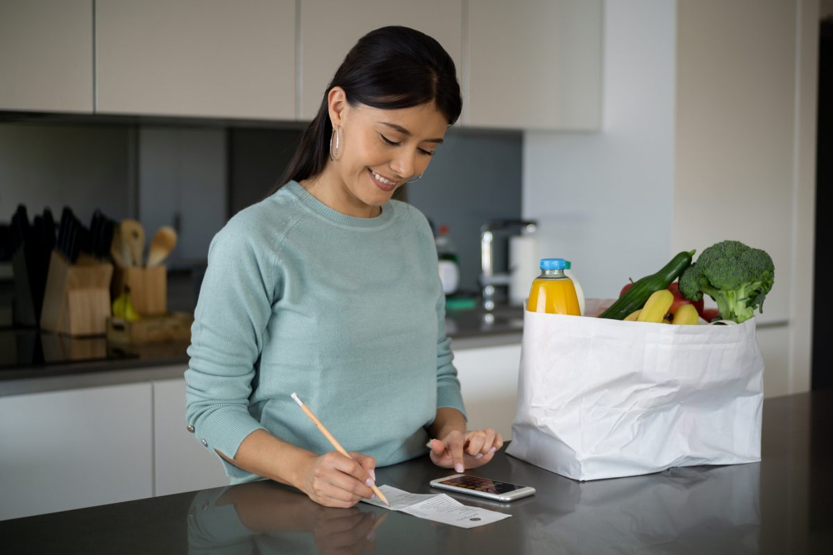 Woman looking at grocery receipt