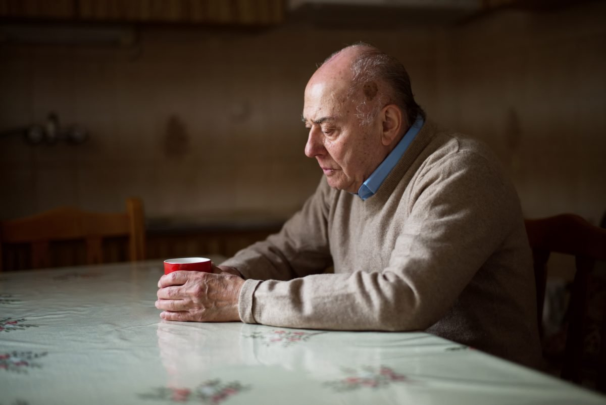 Elderly man alone at table
