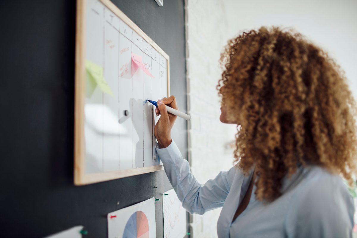 business woman writing in calendar
