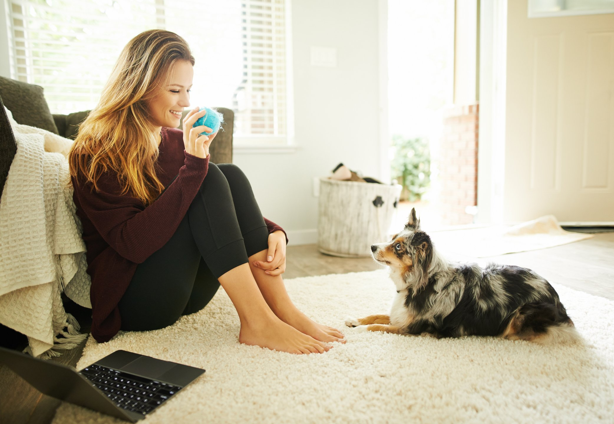 Shot of a young woman spending quality time with her dog at home
