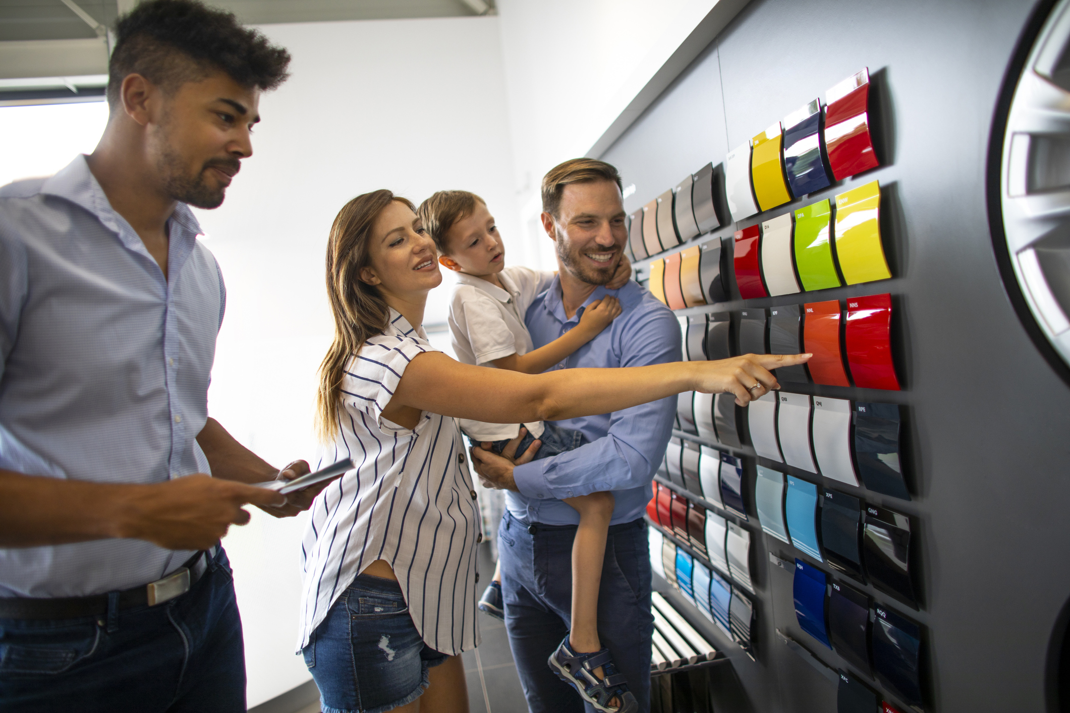 Young multi-ethnic car salesman providing assistance to a family with a young boy in picking out a color for their new car in a car salon.