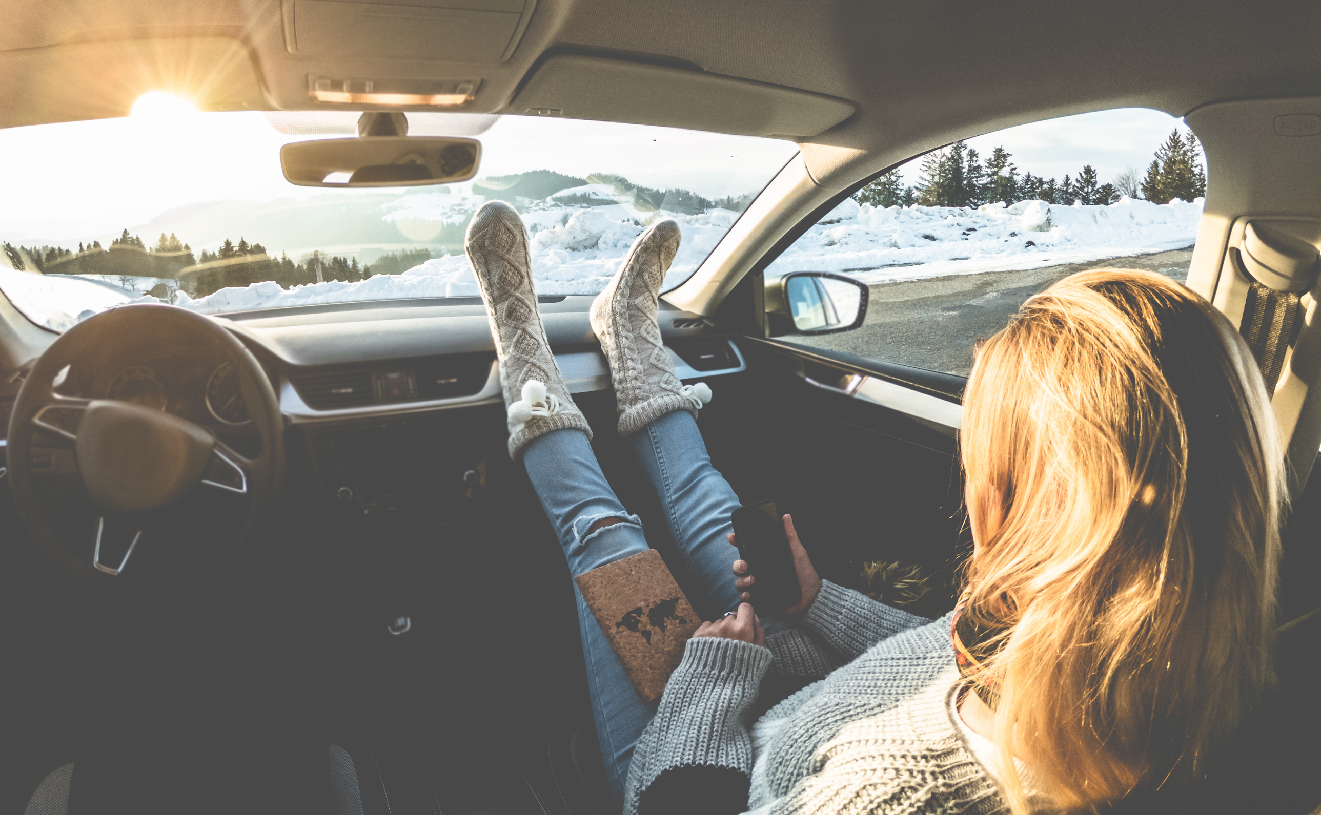 Woman using smartphone inside car with feet warm socks on dashboard - Girl relaxing in auto trip reading travel book with snow mountains in background - Traveler concept - Focus on feet