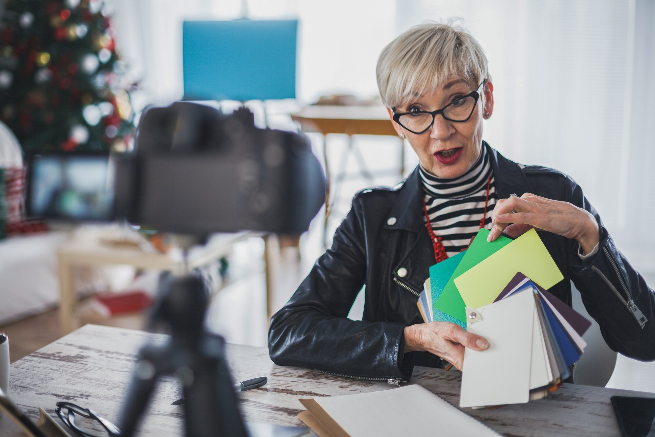 Shot of confident mature female vlogger sitting in her recording studio and showing color swatches to a camera while recording a video for her social media audience.