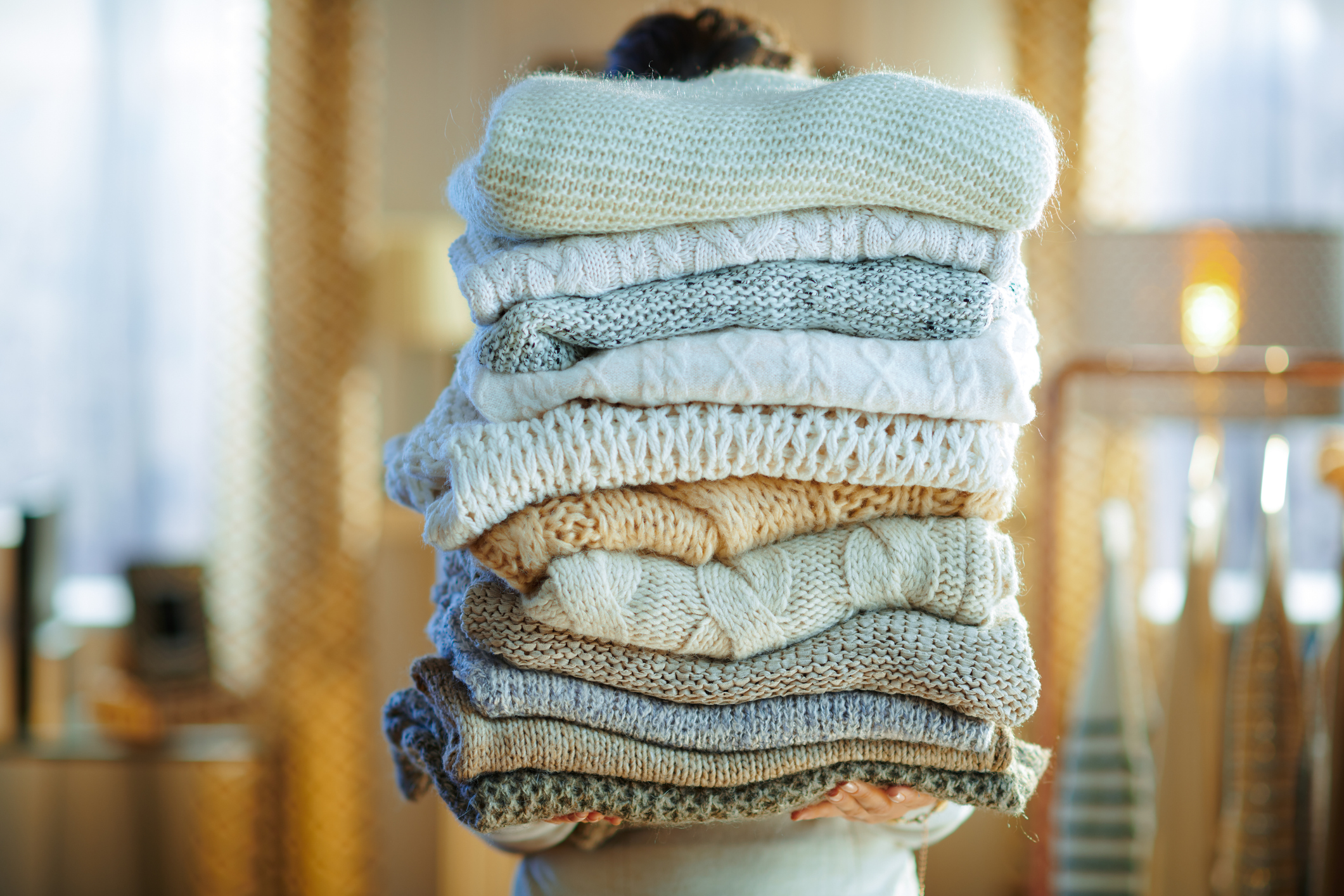 stylish woman in white sweater and skirt in the modern house in sunny winter day holding huge pile of sweaters.