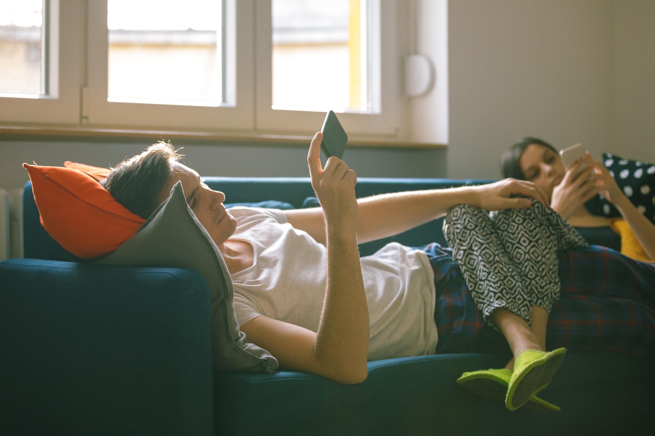 Young couple in pajamas lying on the sofa with legs intertwined and using phones