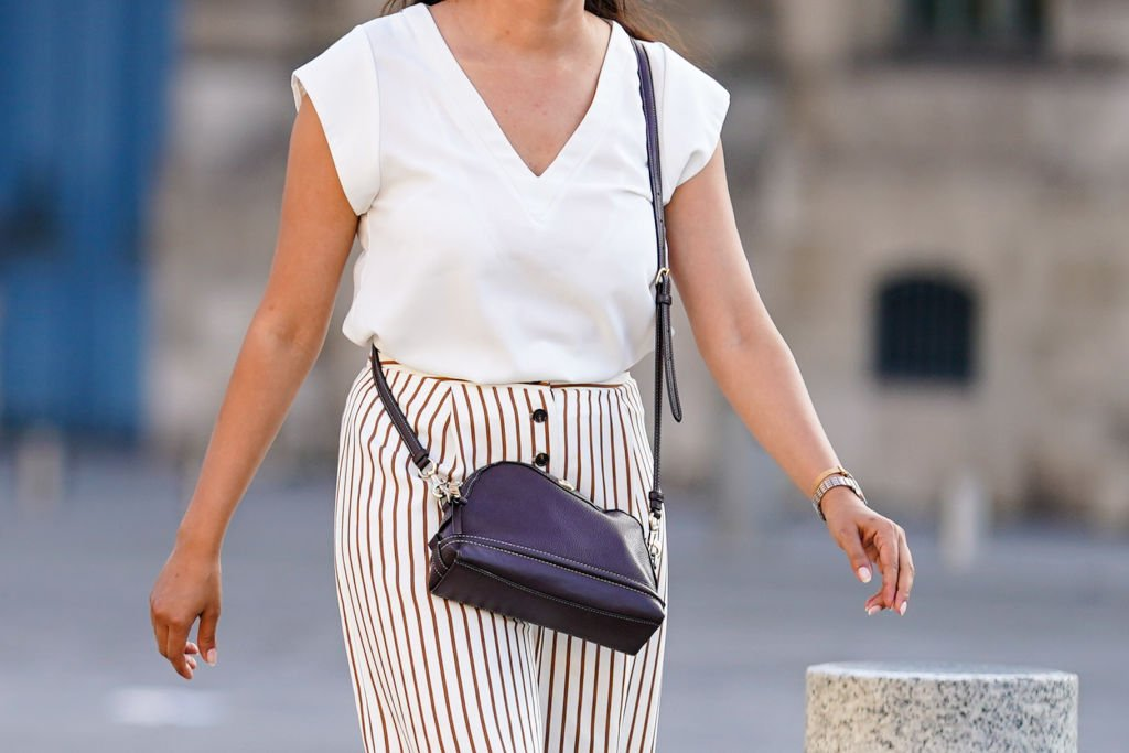 A passerby wears a v-neck white t-shirt, brown and white striped pants, a leather bag, on July 08, 2020 in Paris, France.