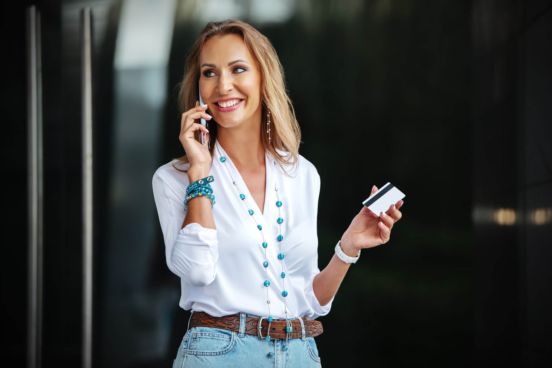 Very happy woman smiling. A stylishly dressed girl stands with a phone in her hand and waves a credit card.