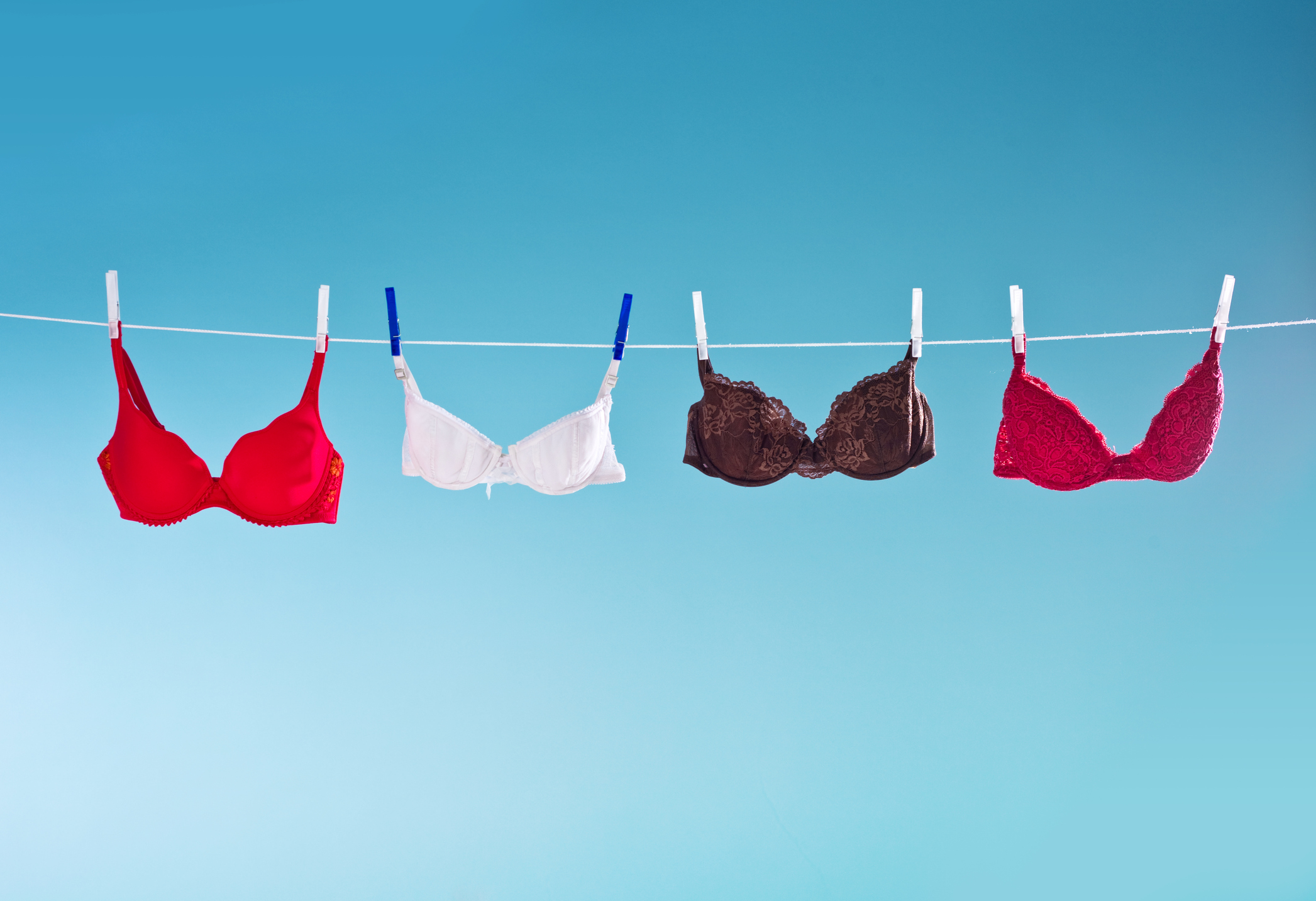 Laundry hangs out on a clothesline to dry. Colorful bras hanging against blue background. Summer time.