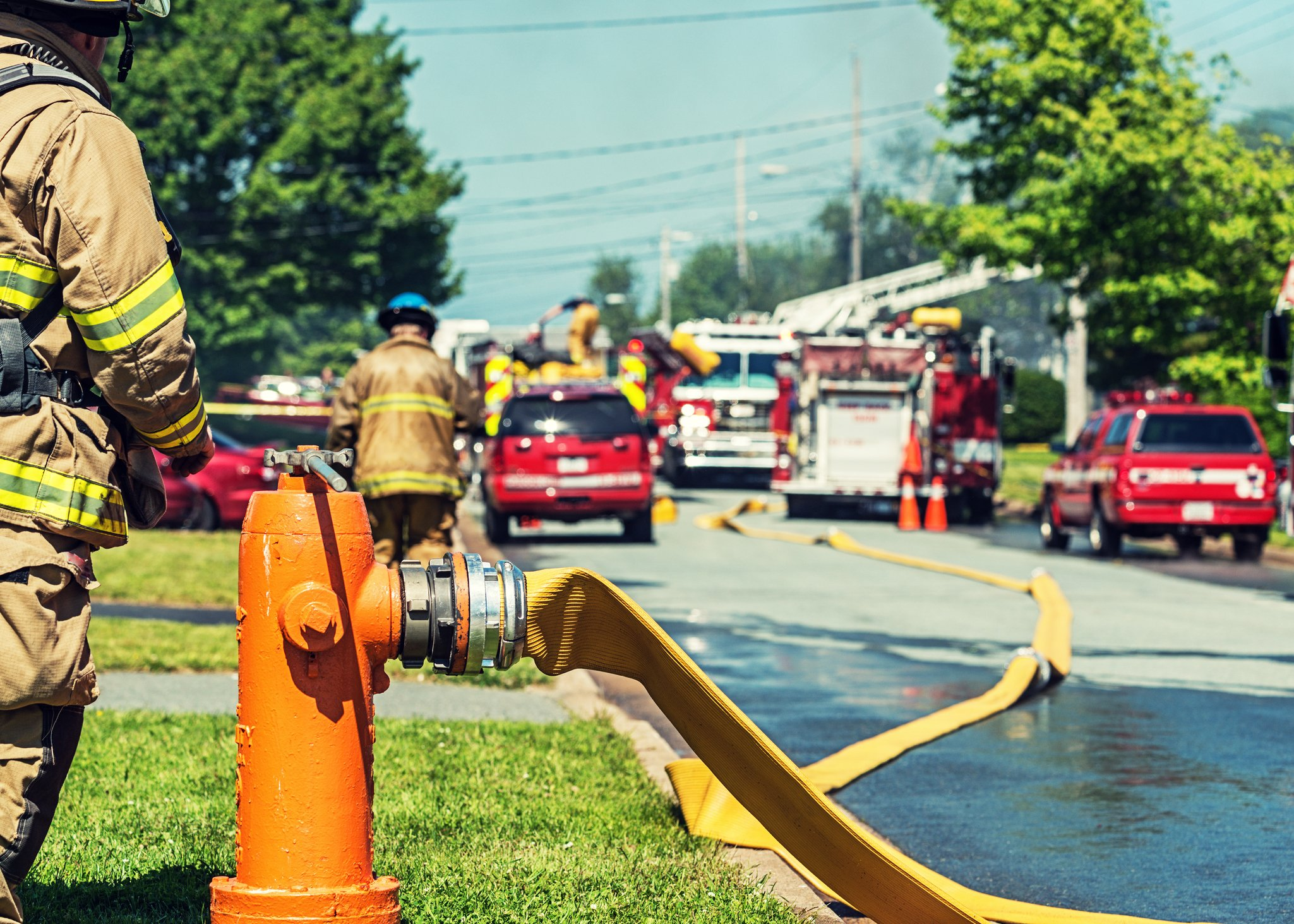 A firefighter stands at ready to turn on a backup fire hydrant on the scene of a house fire.