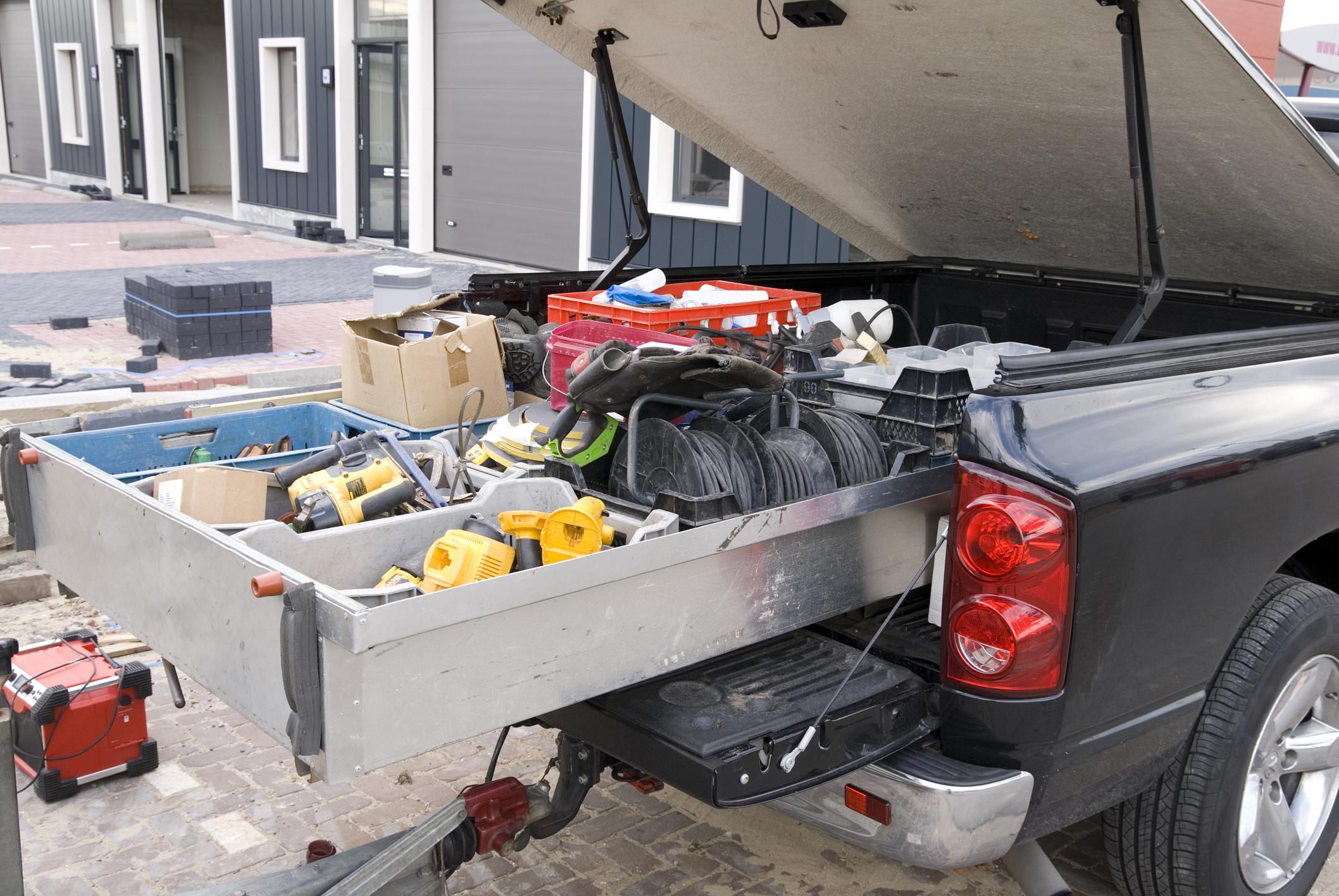 Pick-up truck of a construction worker with a trunk full of tools.