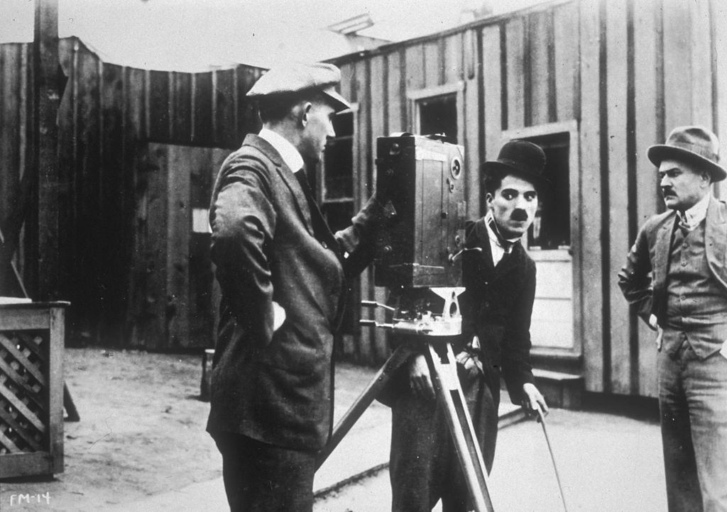 1914: British actor and director Charles Chaplin (1889 - 1977), in costume as the Tramp, looks into a movie camera as two cameramen stand by in a still from director Henry Lehrman's silent film, 'Kid Auto Races at Venice'. It was Chaplin's first screen appearance as the Tramp.