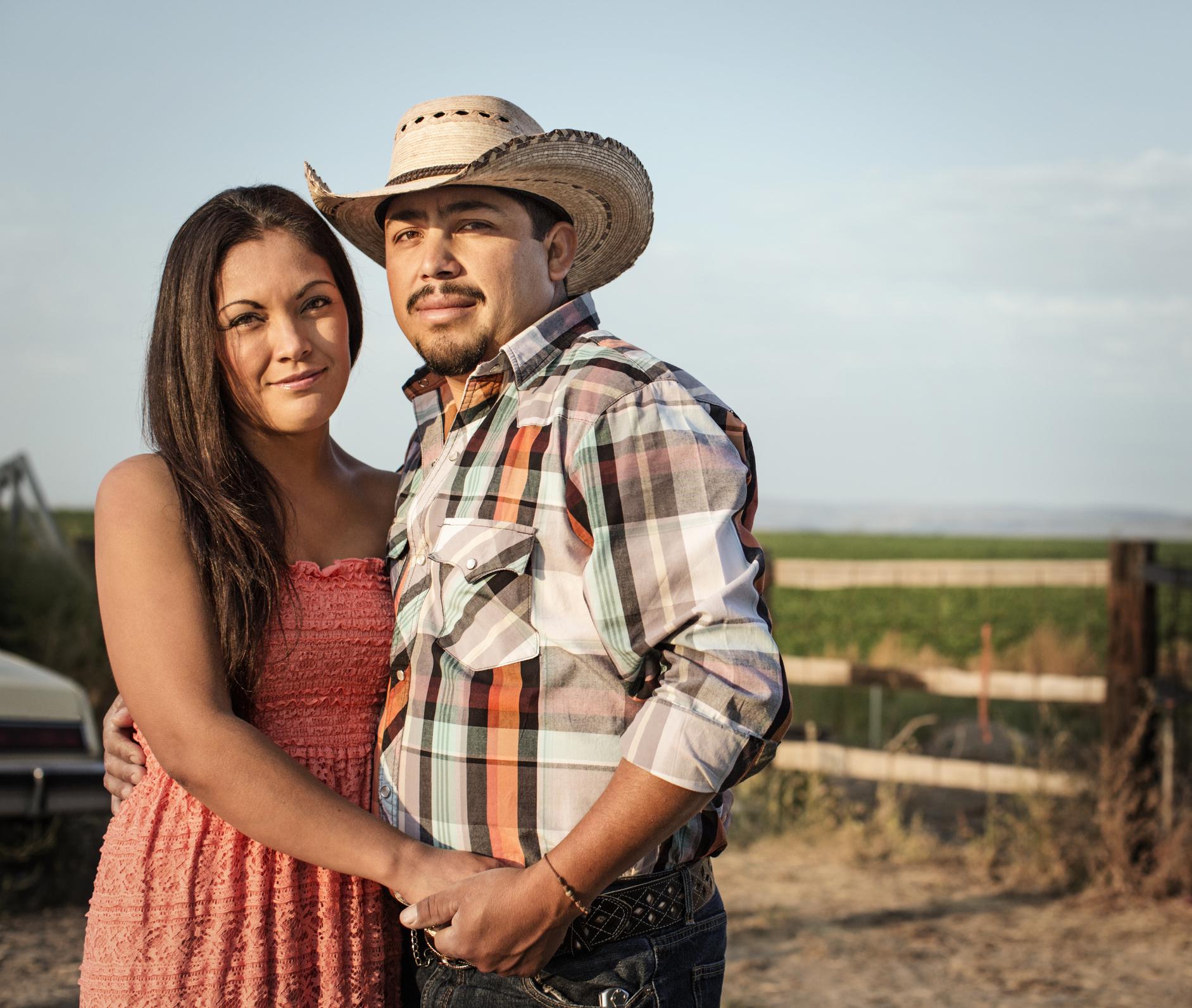 Hispanic couple hugging on ranch