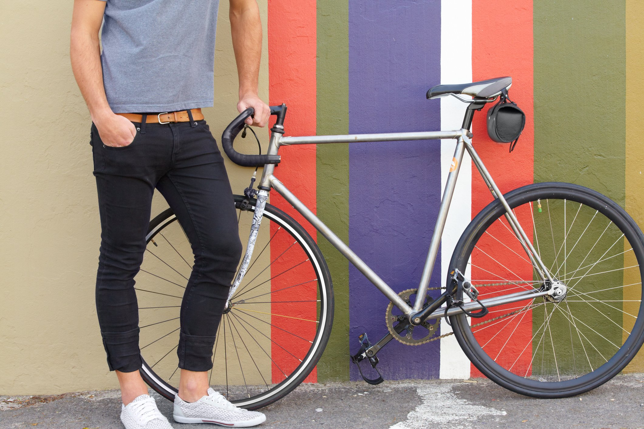 Cropped shot of a stylishly dressed young man standing next to a bicycle against a colourful background