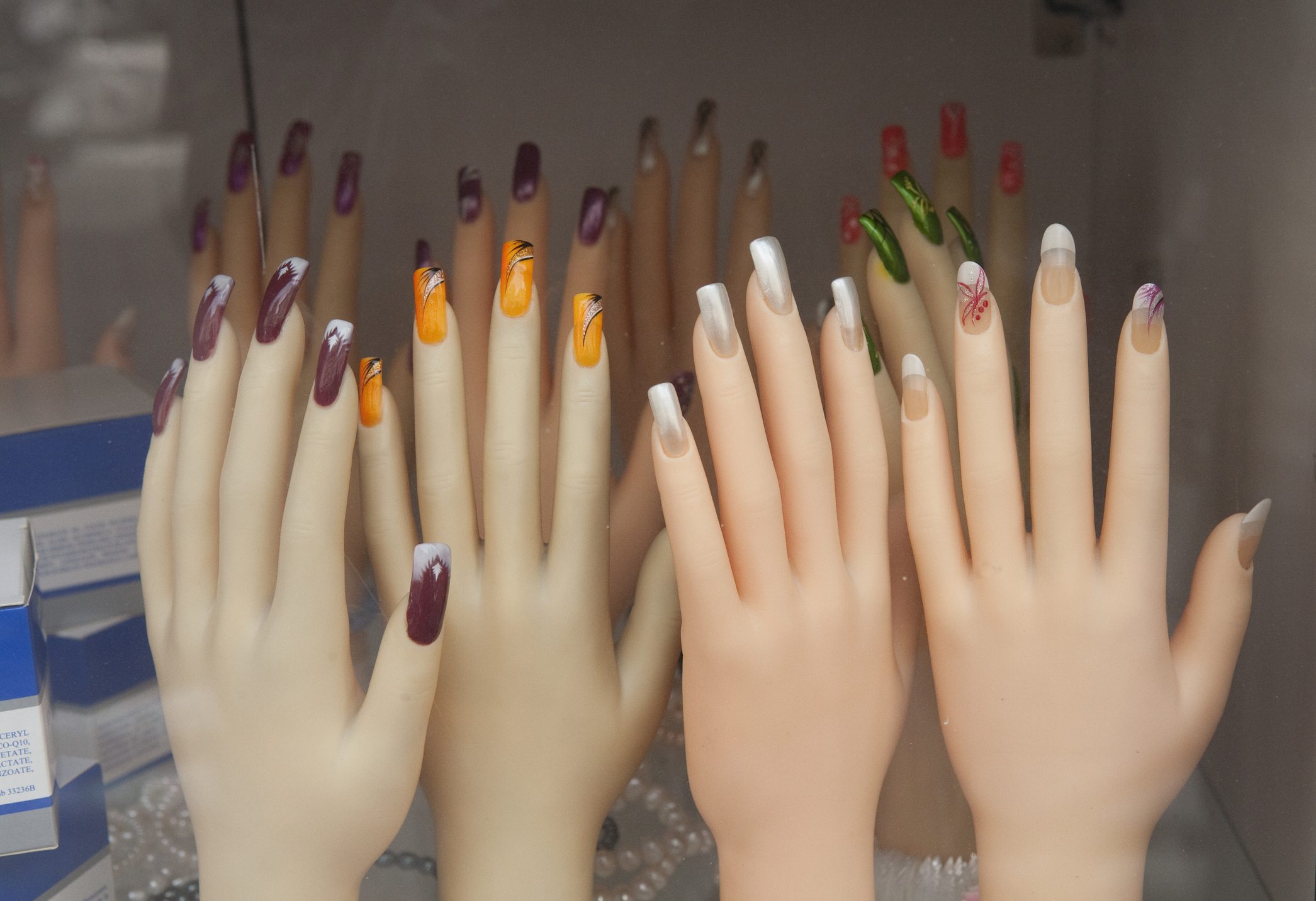 mannequin hands on display in a fingernail decorating shop, showing examples