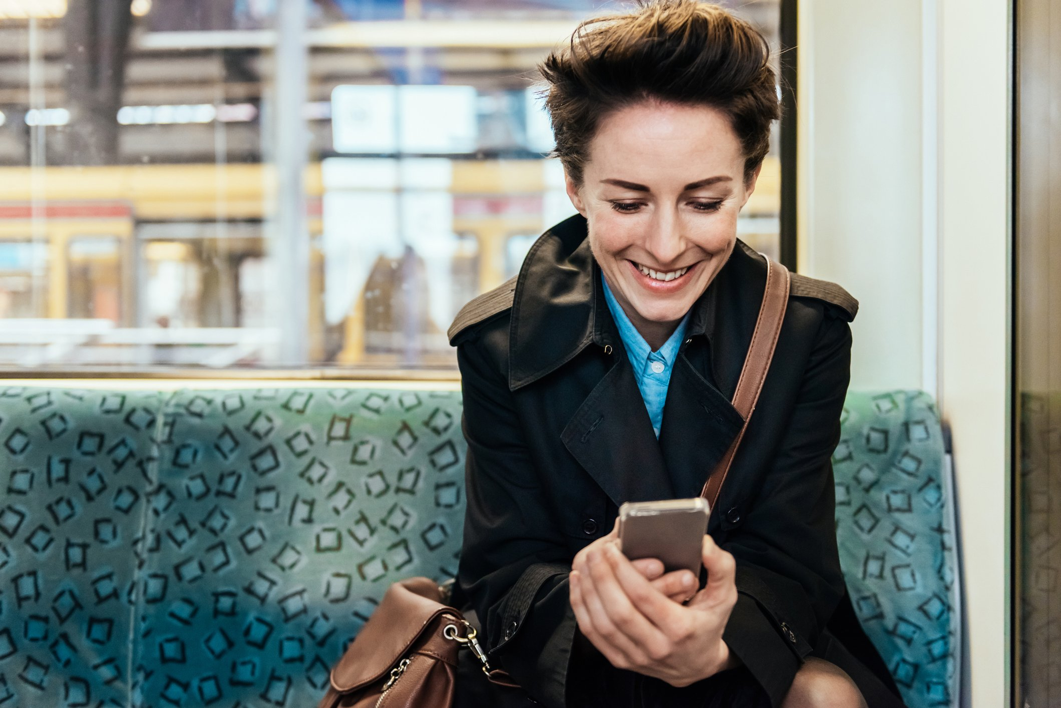 Mature businesswoman checking Messages on her smart phone while commuting in train