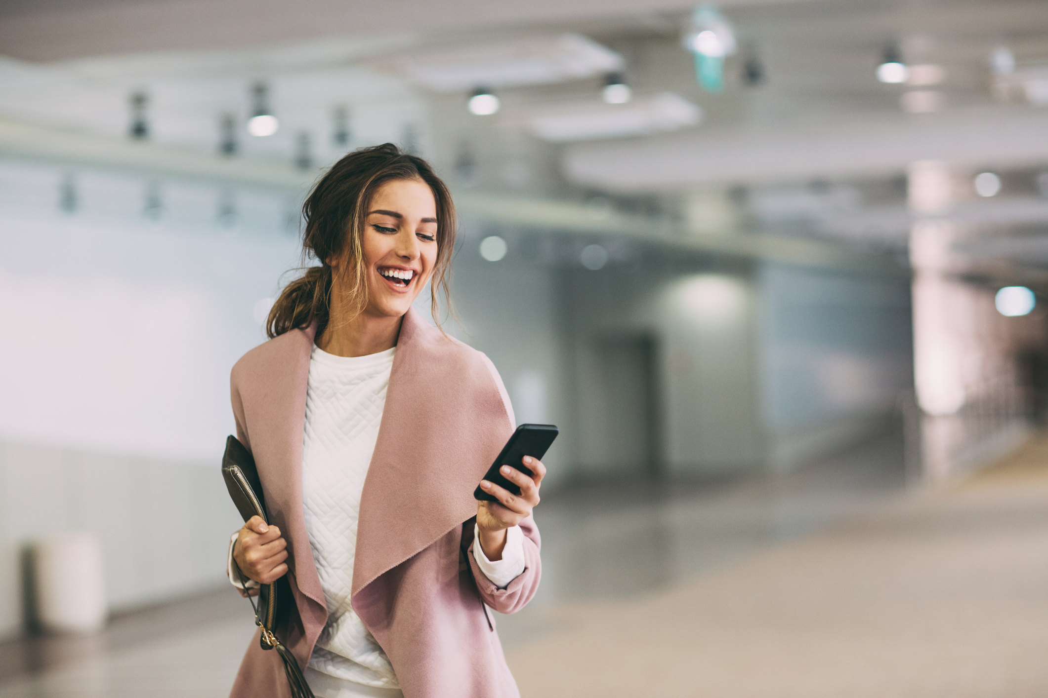 Elegant woman holding a smart phone walking in a subway parking lot, with copy space.