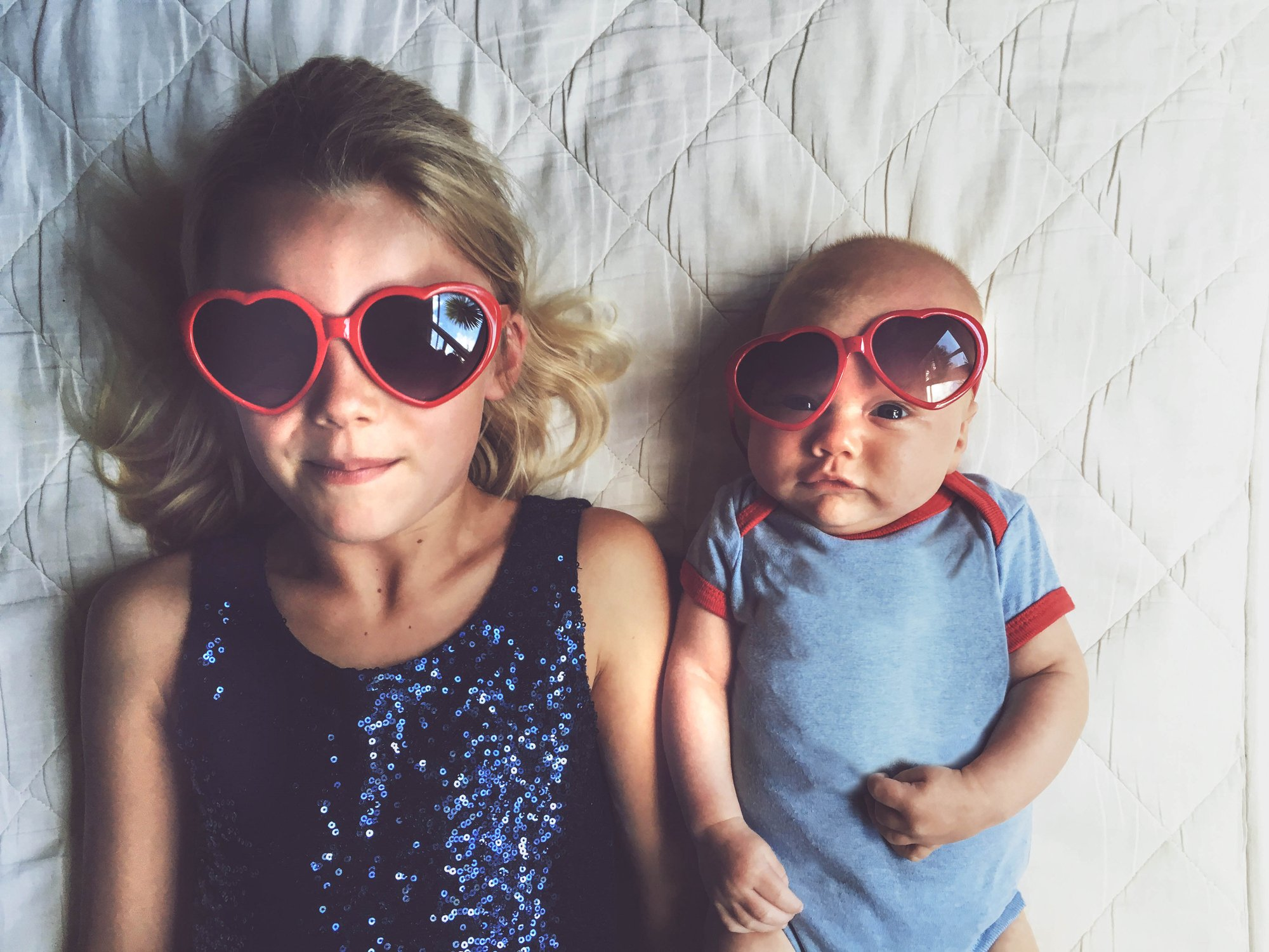 Young girl laying beside baby brother both wearing red love heart glasses