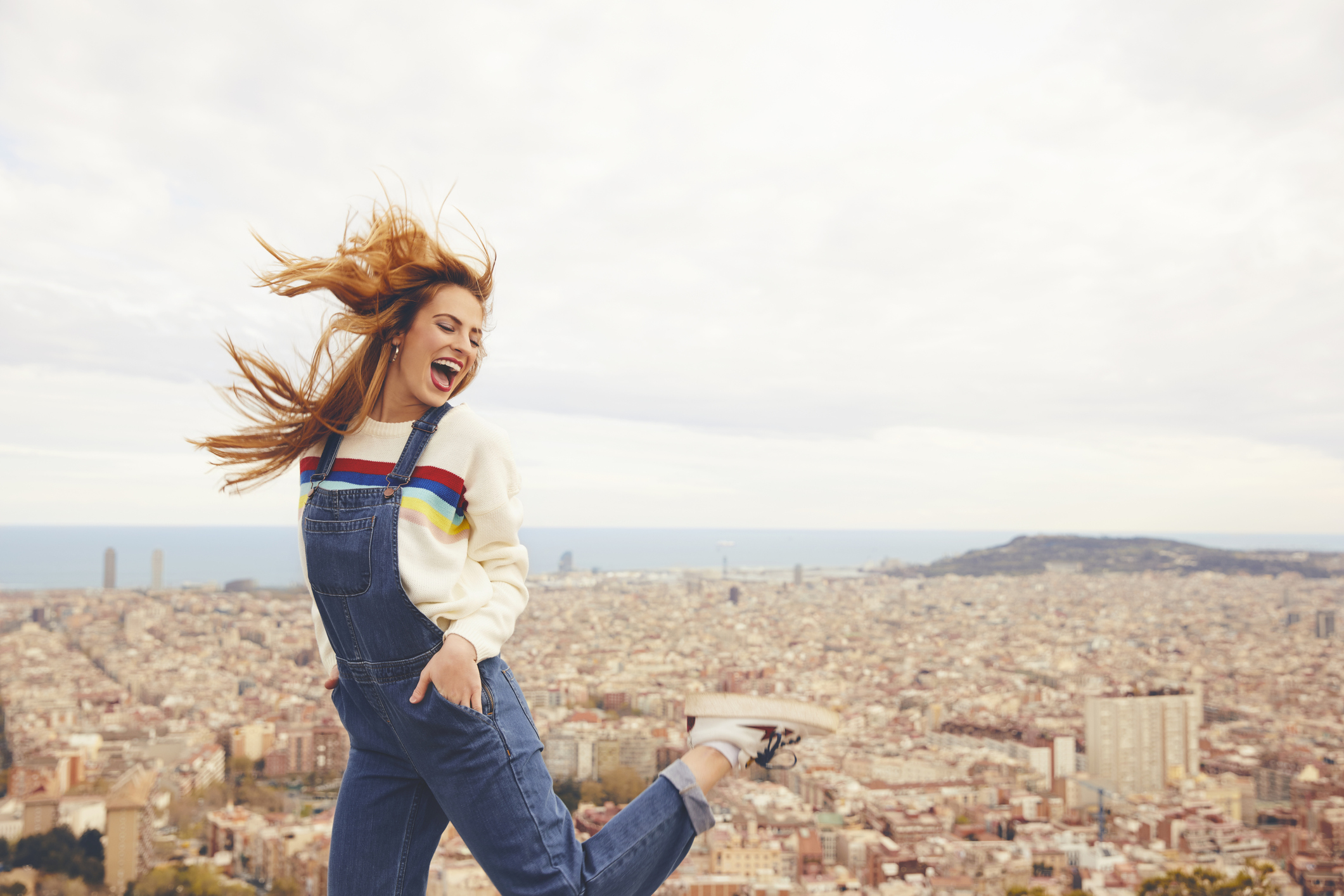 Cheerful woman dancing against cityscape. Happy female is wearing bib overalls. She is enjoying vacations.