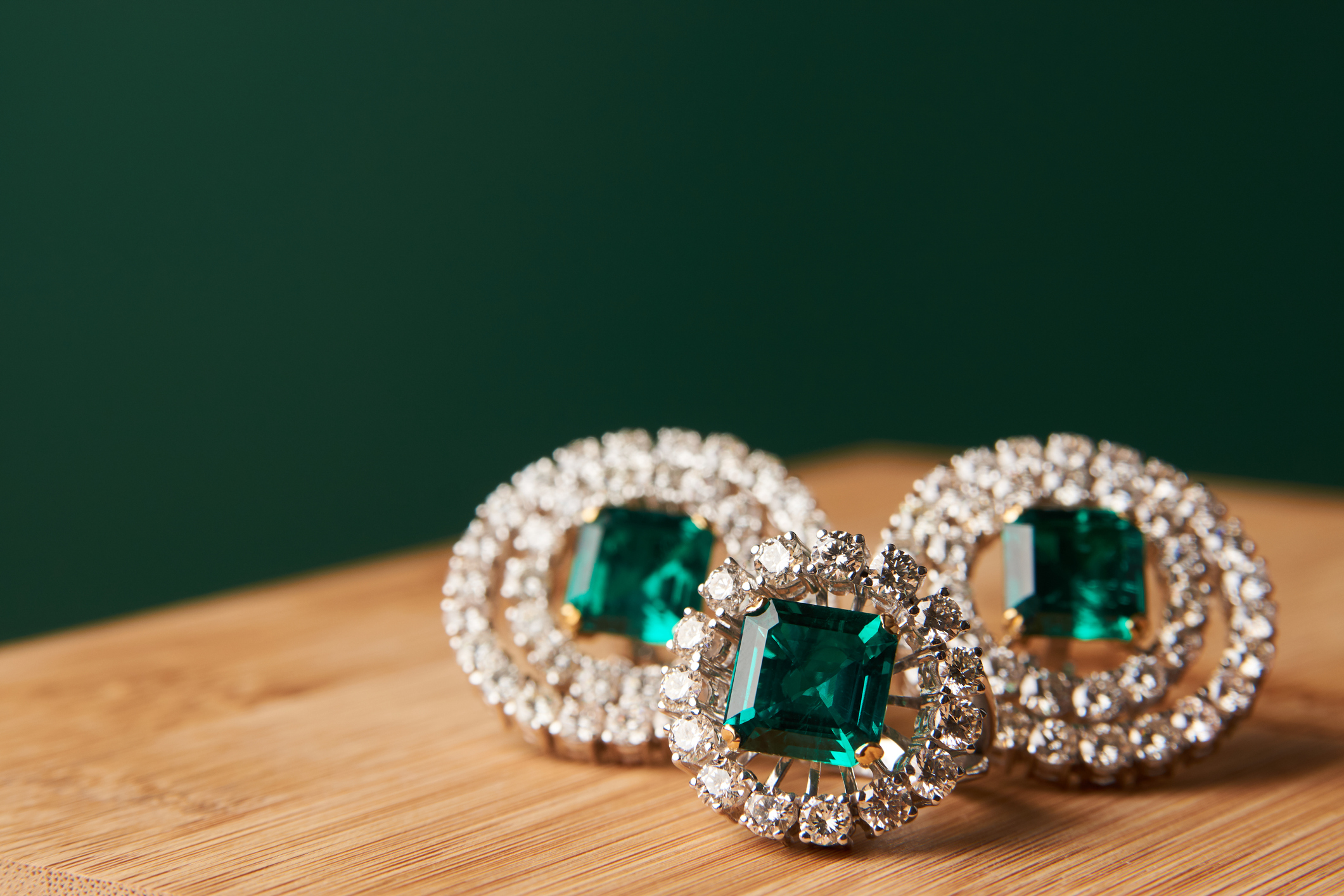 Emerald ring and pair of diamond earrings in gold, wedding jewelry with luxury gift box , close-up. Selective focus