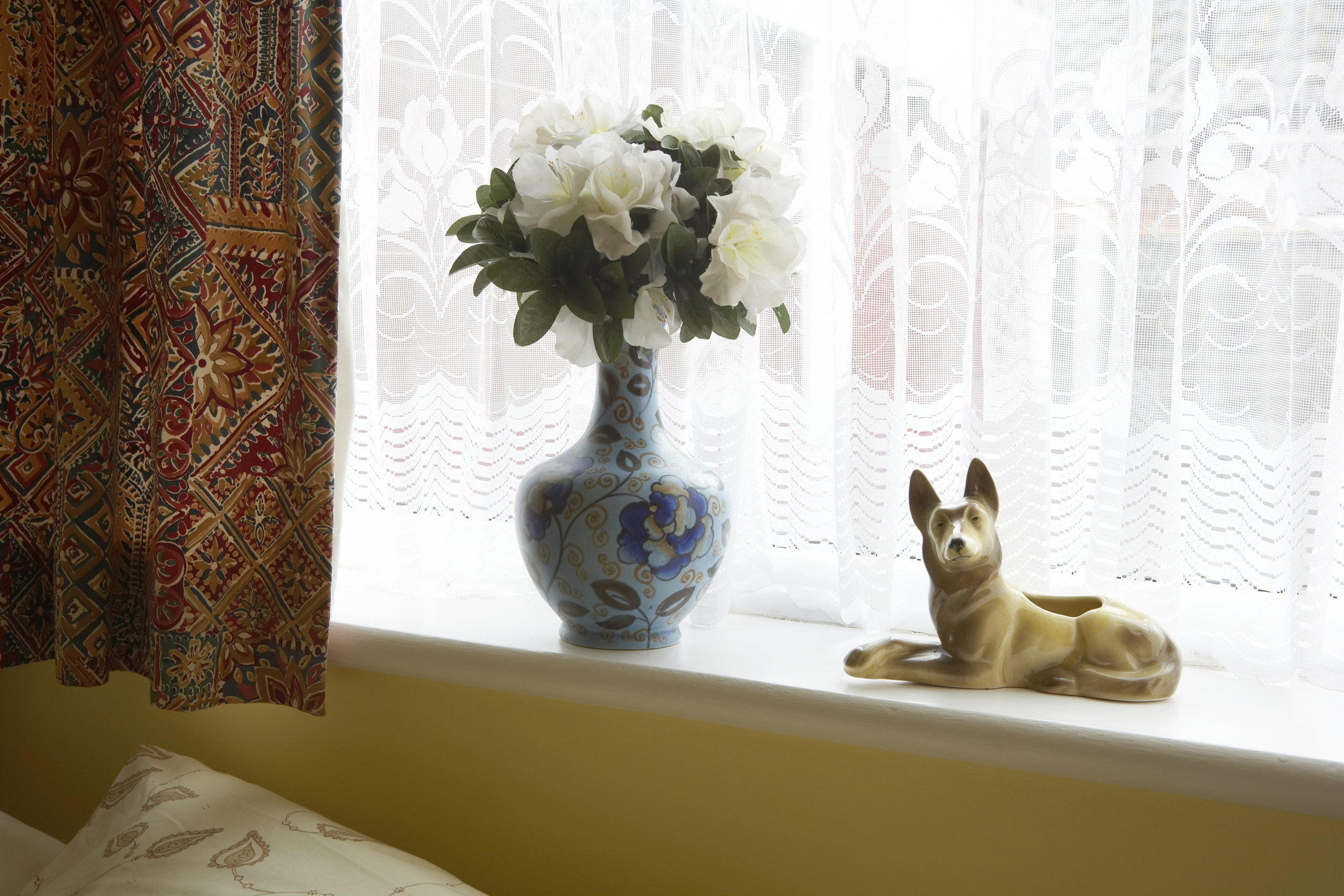 Porcelane dog and vase of flowers on window sill