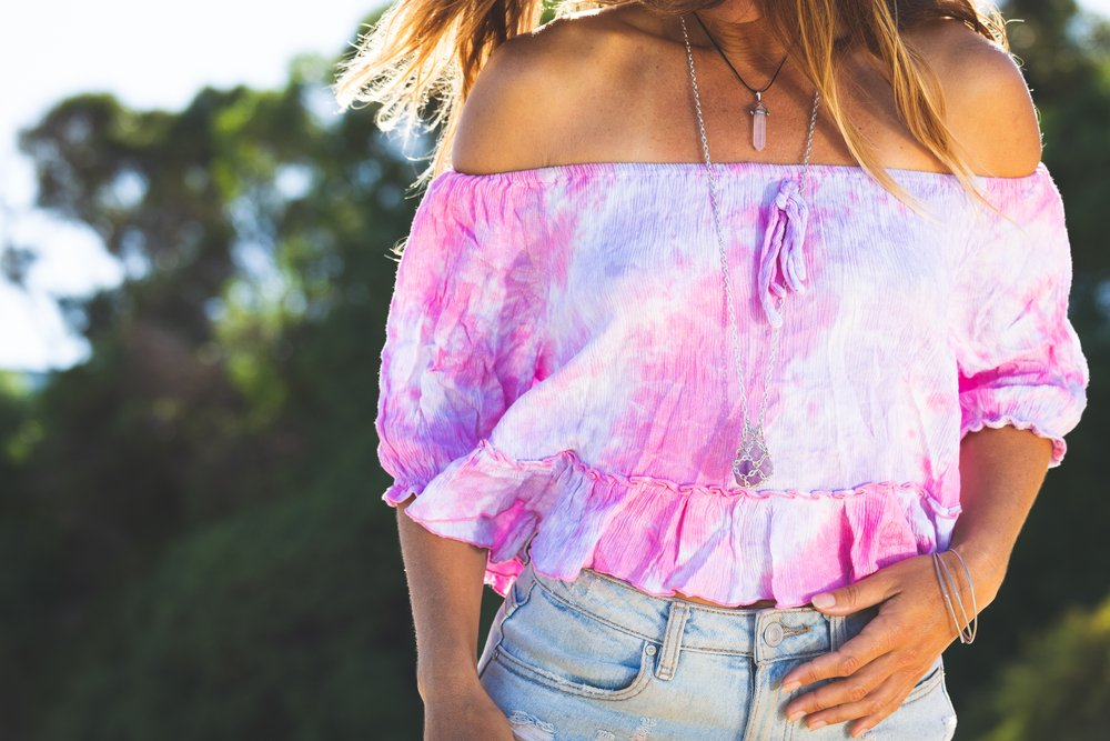 Young woman wearing pink summer crop top and crystal necklaces at the beach on sunny day