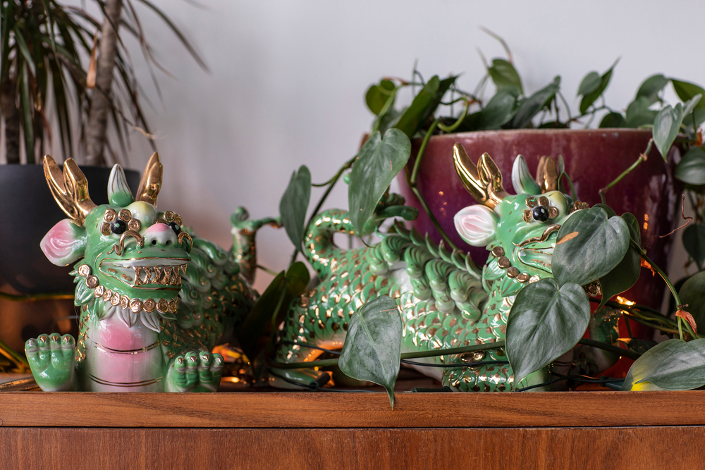 A detail of two green and gold traditional Chinese ceramic dragon statues in a city loft interior