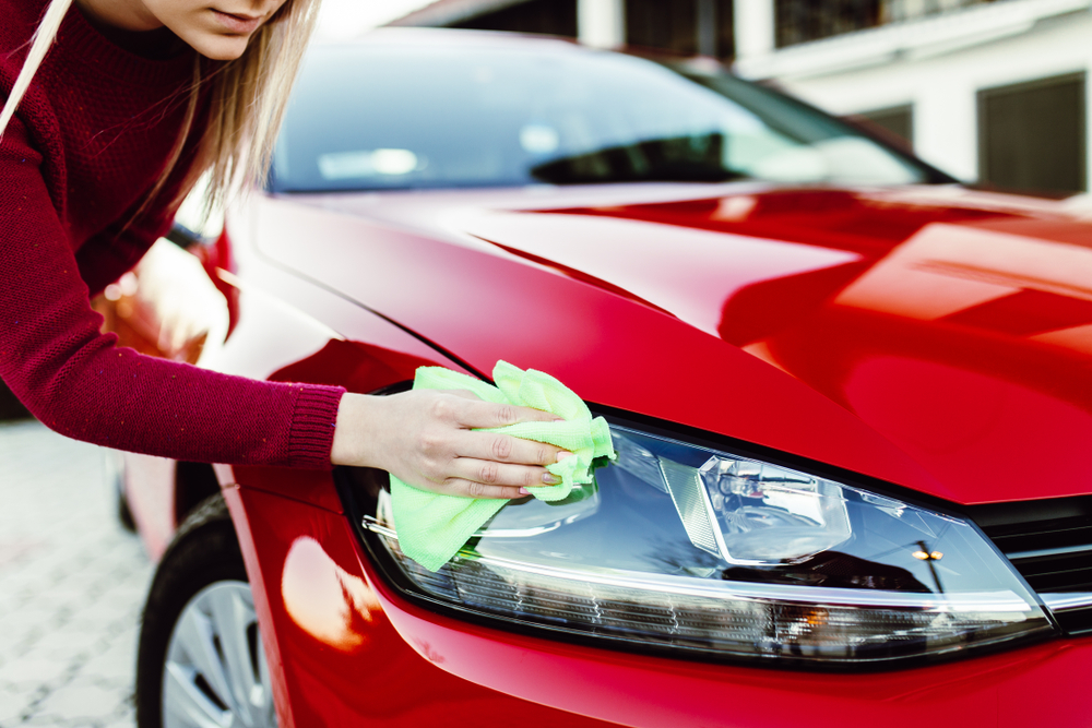 Young woman cleaning car with microfiber cloth, car detailing (or valeting) concept.