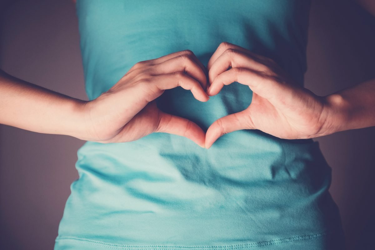 heart-shaped hands over stomach