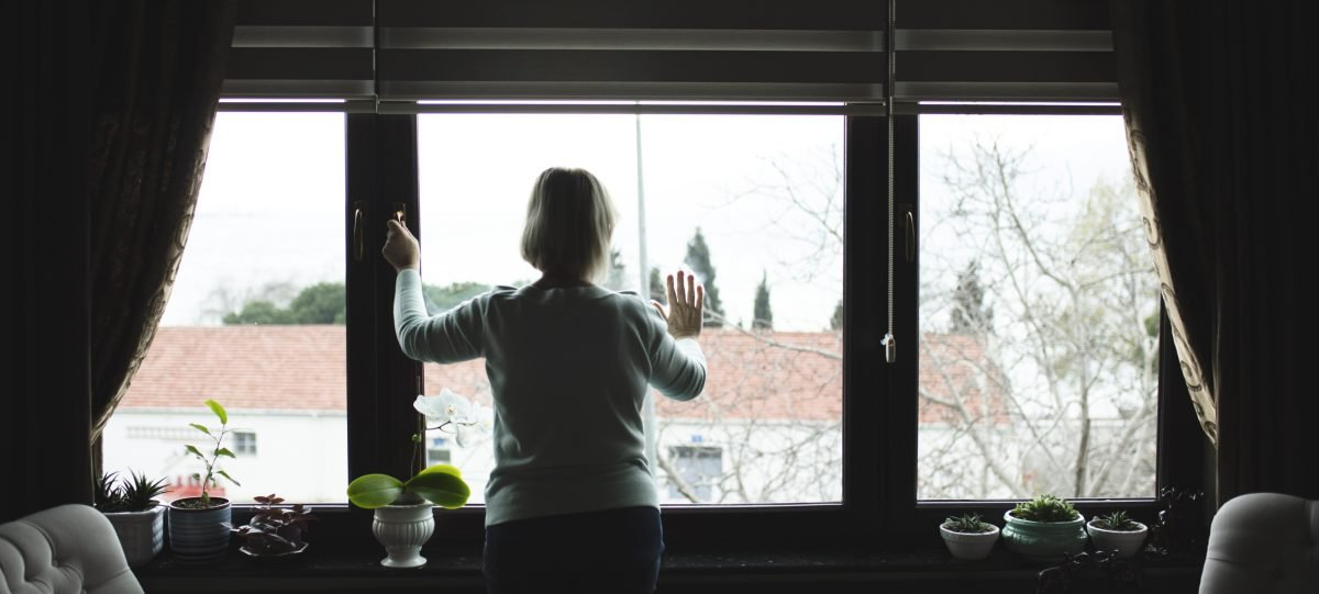 Lonely woman looking through window