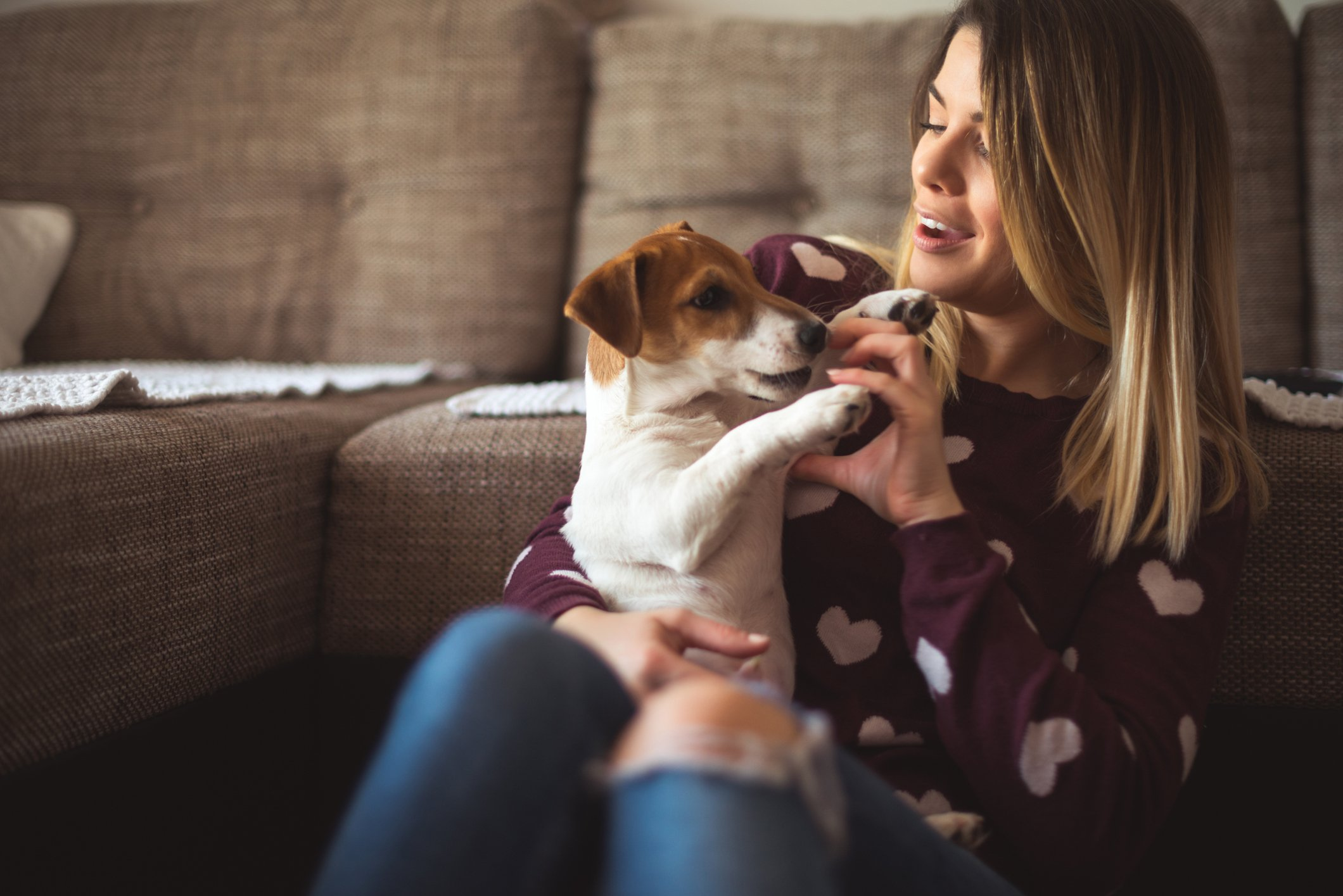 Beautiful girl playing with her dog at home.