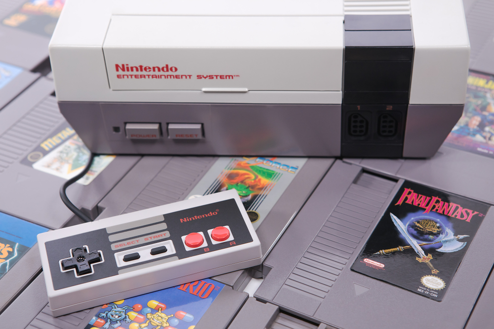 A Nintendo NES console system and controller on top of some game cartridges